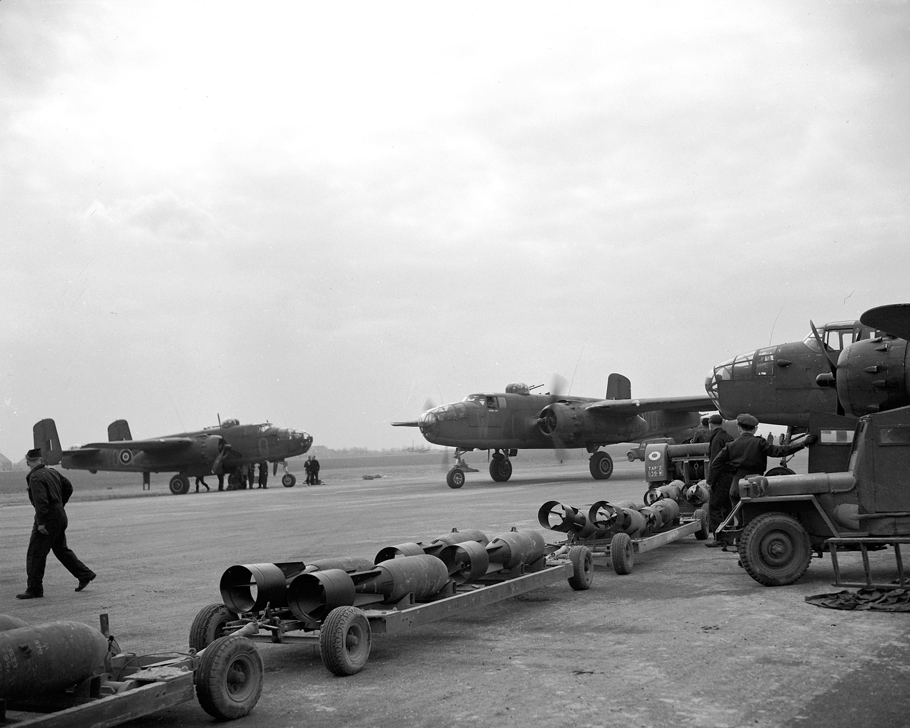 At an undisclosed airfield in England, tractors and trailers loaded with high-explosive bombs await incoming Mitchell light bombers crewed by Royal Canadian Air Force members on February 14, 1945. PHOTO: DND, PL-42718