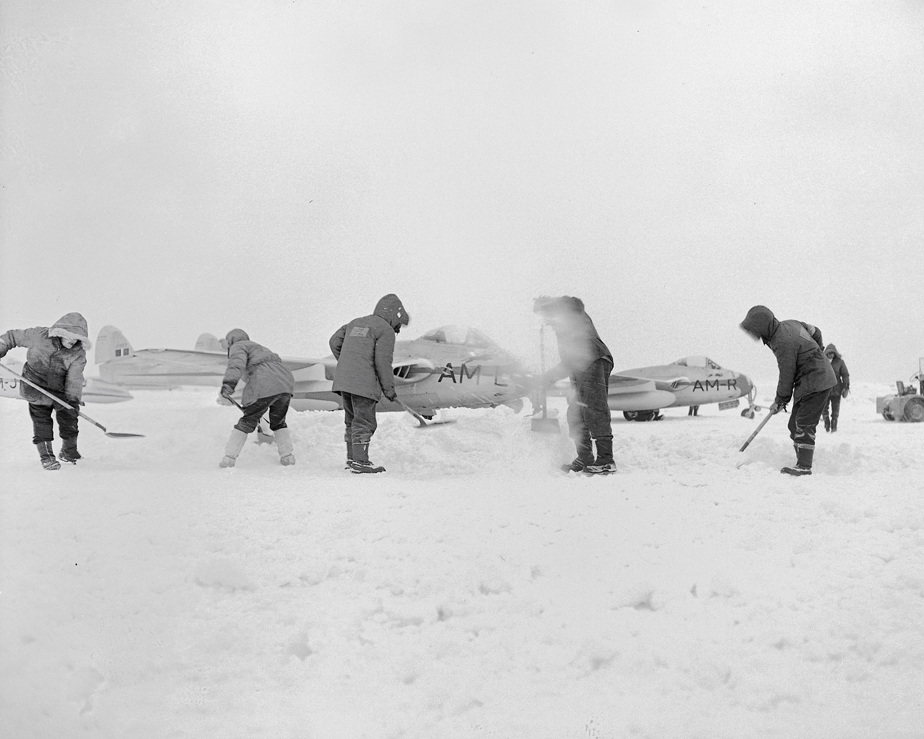 On February 14, 1950, at an undisclosed location, personnel spend St. Valentine's Day clearing snow away from Royal Canadian Air Force DH-100 Vampire aircraft. PHOTO: DND Archives, PL-50325