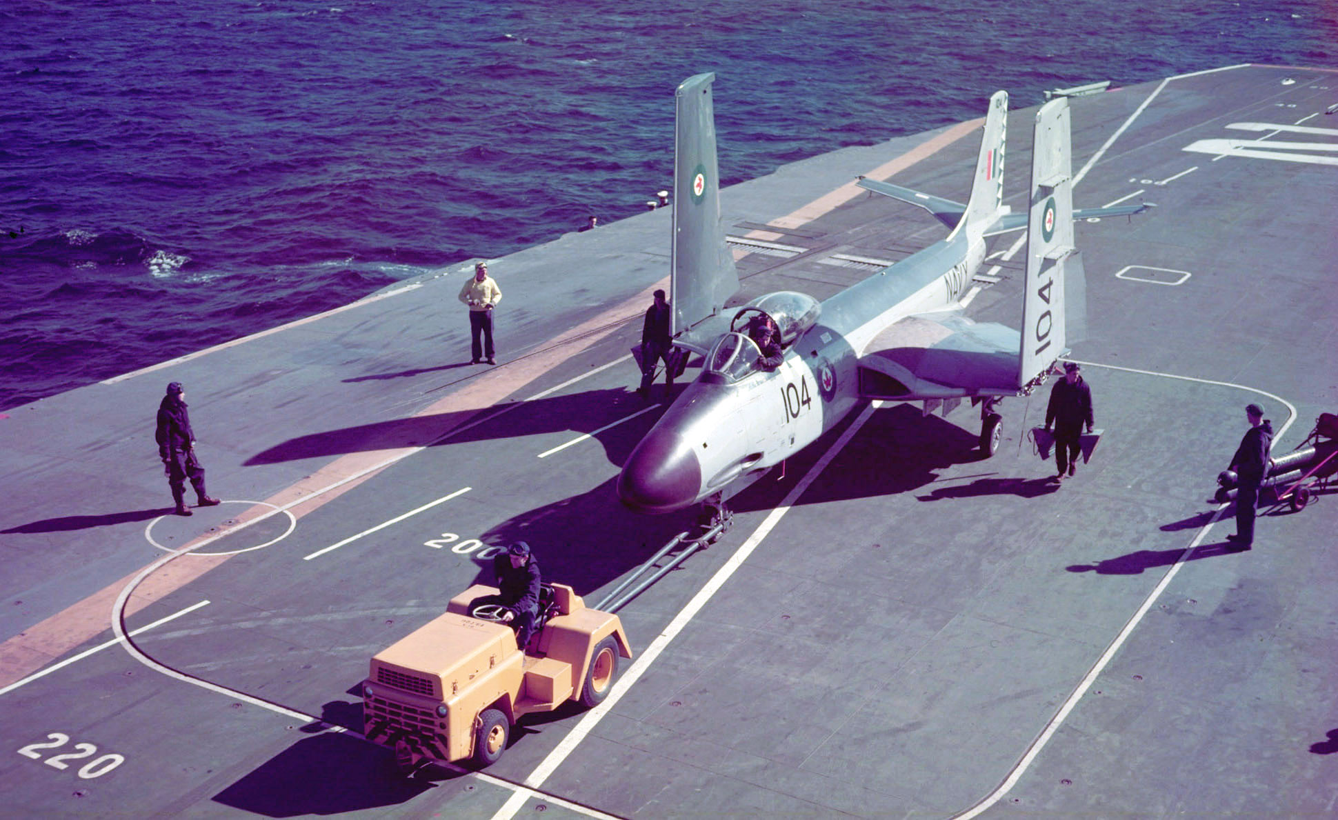 "A McDonnell F2H-3 Banshee fighter jet, with its wings folded, is pulled by a ""mule"" on the flight deck of Her Majesty's Canadian Ship Bonaventure. Lieutenant Barry Troy was enroute back to the Bonnie on February 25, 1958, near Naval Station Mayport in Florida, when he encountered an unexpected fog bank. His Banshee crashed, and he was never seen again. PHOTO: DND Archives, CT-623"