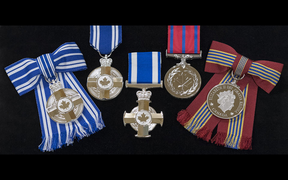 Five medals on ribbons on a black background