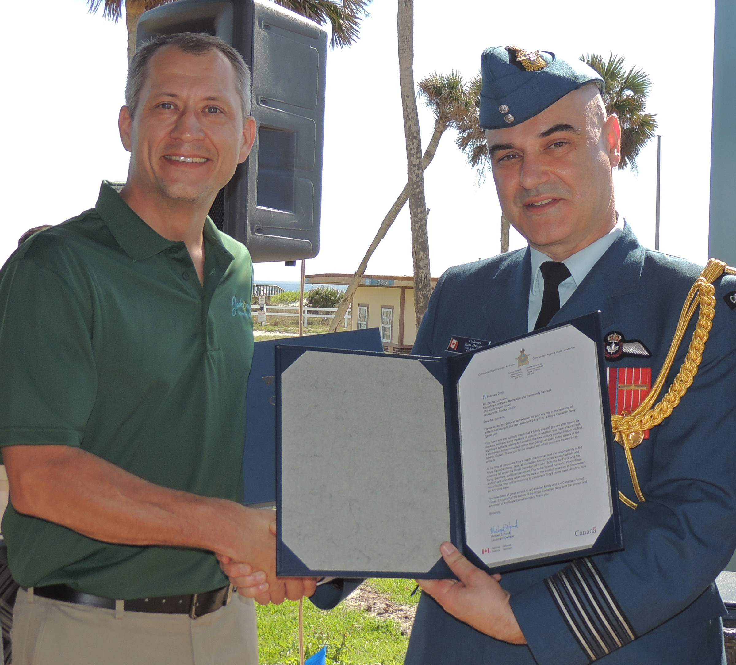 Colonel Tom Dunne (right), the Canadian air attaché at the Embassy of Canada in Washington, presents a letter of thanks signed by the commander of the Royal Canadian Air Force, Lieutenant-General Michael Hood, to Jacksonville park ranger Zach Johnson. Ranger Johnson first discovered the bundle of debris that turned out to be the parachute, life jacket and other items that had been worn by Lieutenant Barry Troy when he disappeared off the coast of Florida on February 26, 1958. PHOTO: Joanna Calder, RCAF public affairs