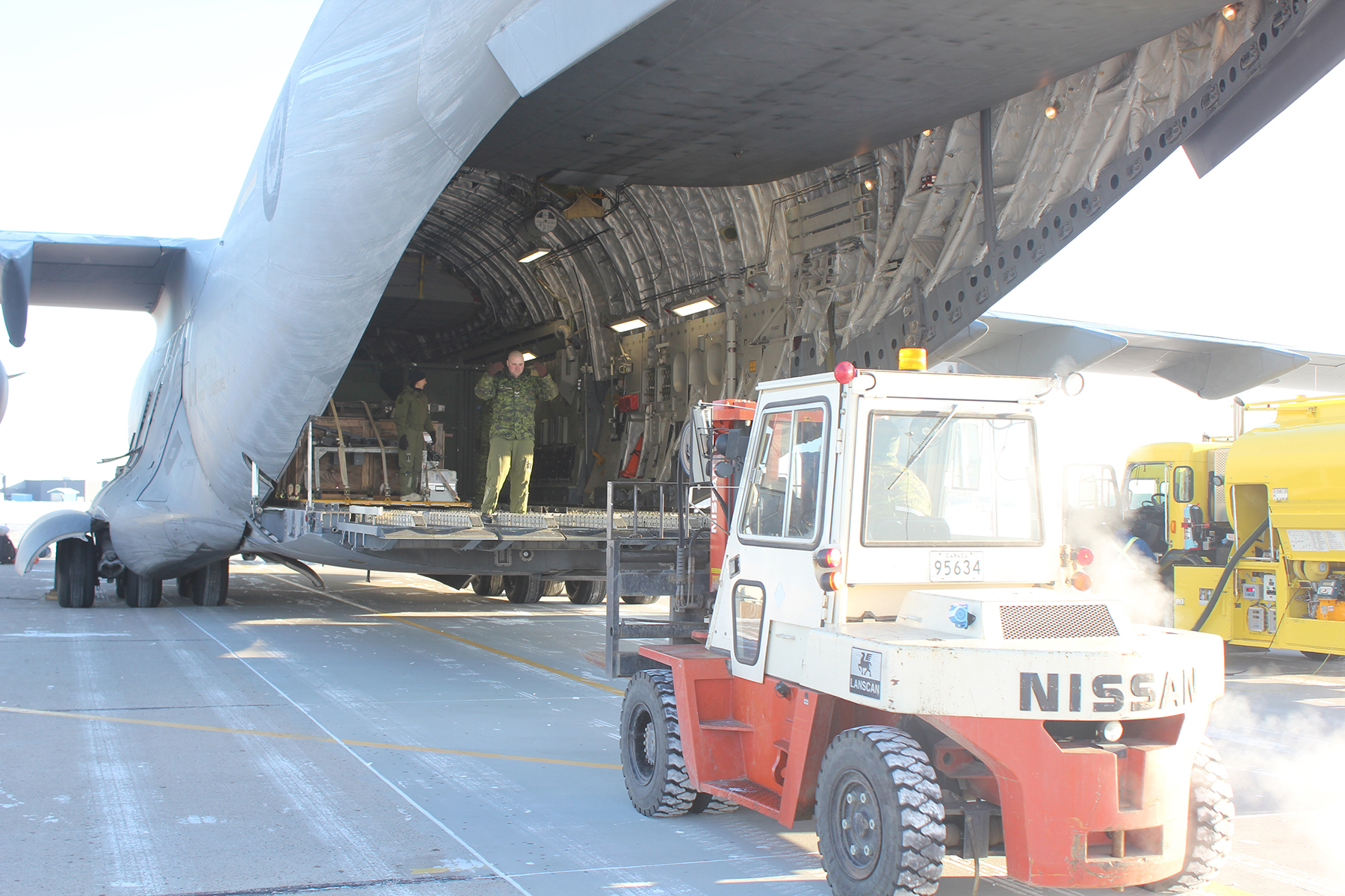 A front-end loader positions itself behind the open cargo ramp of a large aircraft.