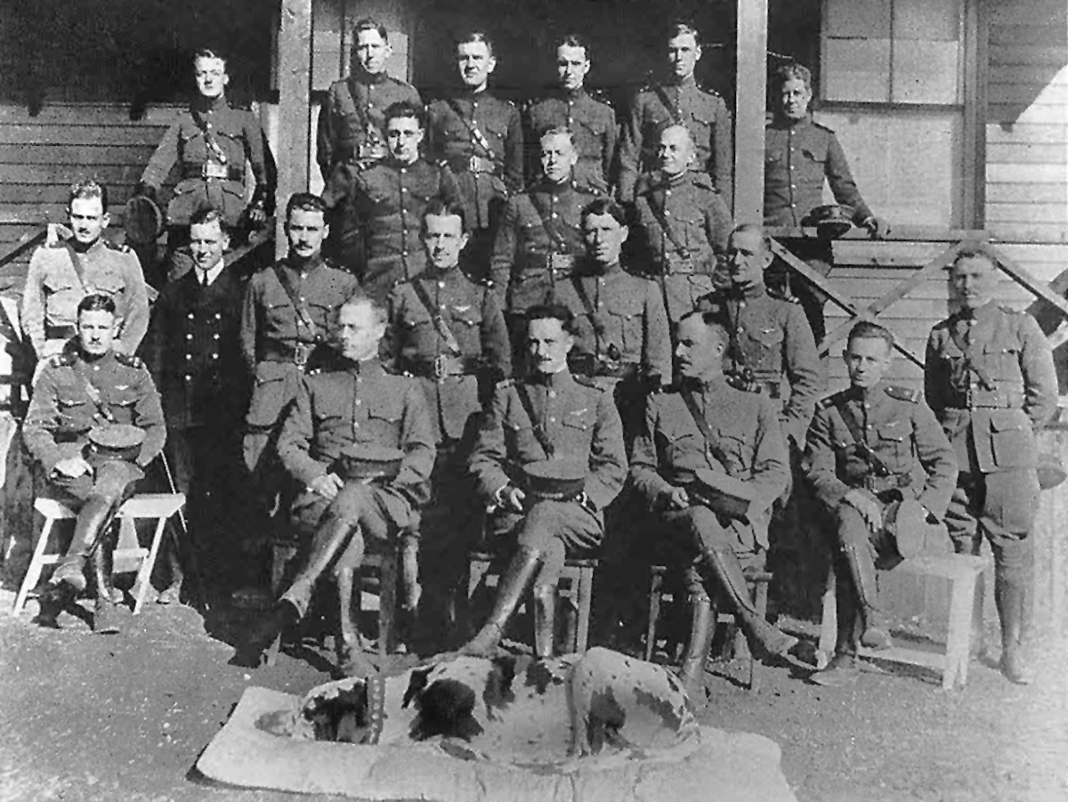 Twenty men in uniform and one man in a suit stand on the porch of a wooden building or sit on wooden chairs, with a dog lying in the foreground.