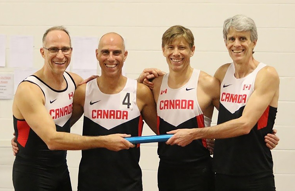 Four men in sports clothes stand in line with their arms around each other's shoulders; two hold a baton.