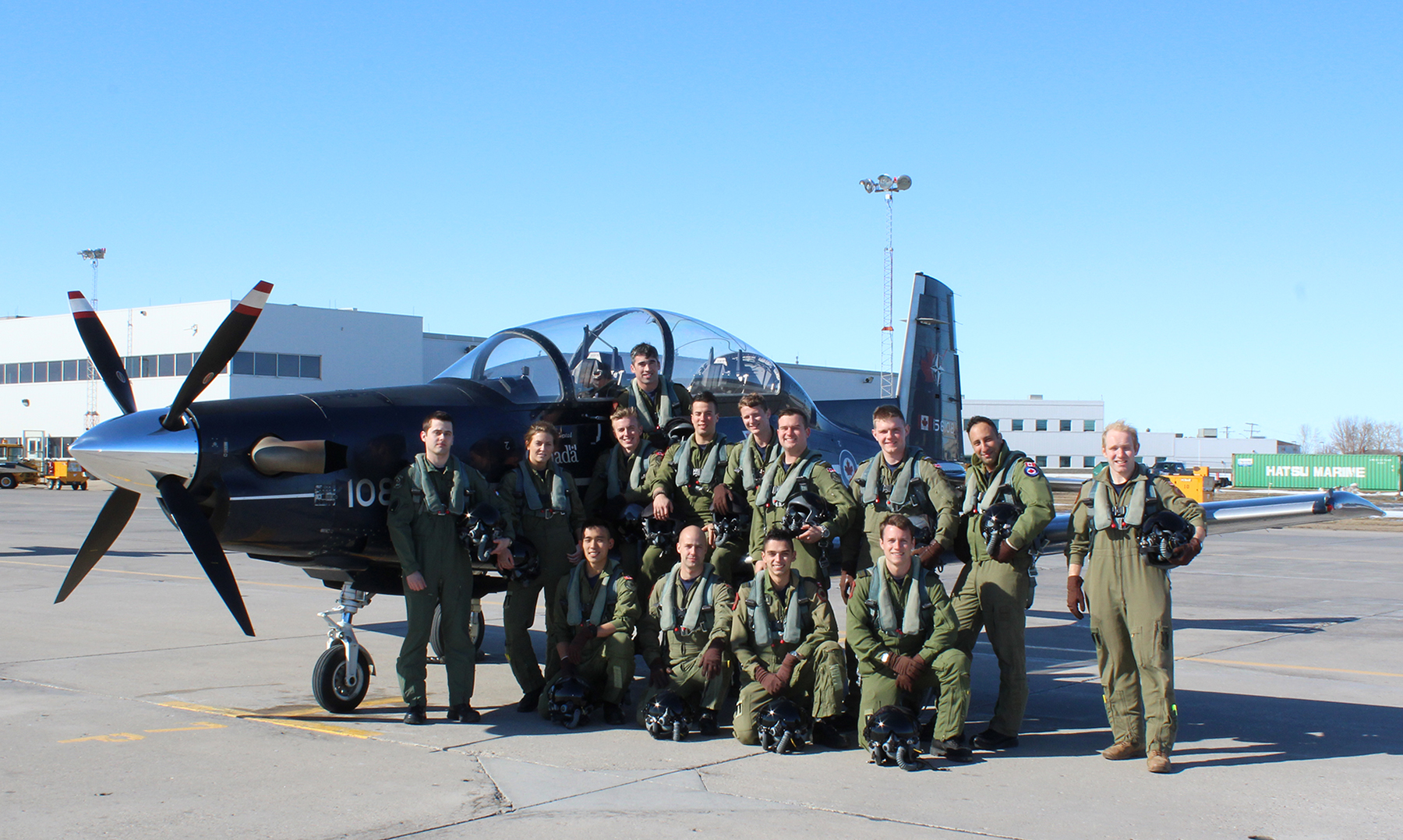 Fourteen young people wearing olive green flight suits and holding helmets gather on and in front of the port wing of a small dark blue aircraft.