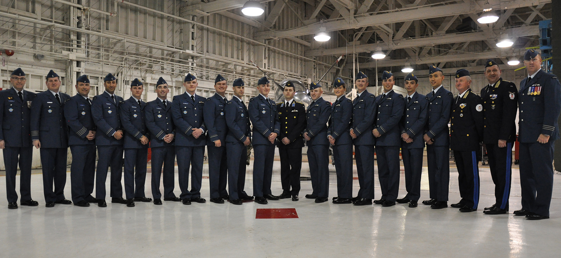 RCAF officers and officers of other Air Forces associated with the NATO Flying Training in Canada Program at 2 Canadian Forces Flying Training School, 15 Wing Moose Jaw, Saskatchewan, gather with the most recent graduates of the program. From left:  Master Warrant Officer Antone Collins, Colonel Dennis O'Reilly, Colonel William Radiff, Lieutenant Mena Ghabbour, Lieutenant Egon Urquhart-Gagne, Lieutenant Christopher Brown, Lieutenant Patryk Kitrys, Lieutenant Thomas Black, Lieutenant Danyk Barrette, Lieutenant Filip Konieczny, Second Lieutenant Mate Hernadi (HuAF), Lieutenant Baron Hordo, Lieutenant Kathryn Rowe, Lieutenant Olivier Demers, Lieutenant Benjamin Rouette, Lieutenant Jordon Gjelsvik, Lieutenant Andre Bui, Brigadier General Albert Safar (HuAF), Brigadier General Csaba Ugrik (HuAF), and Lieutenant-Colonel David Smith. PHOTO: DND