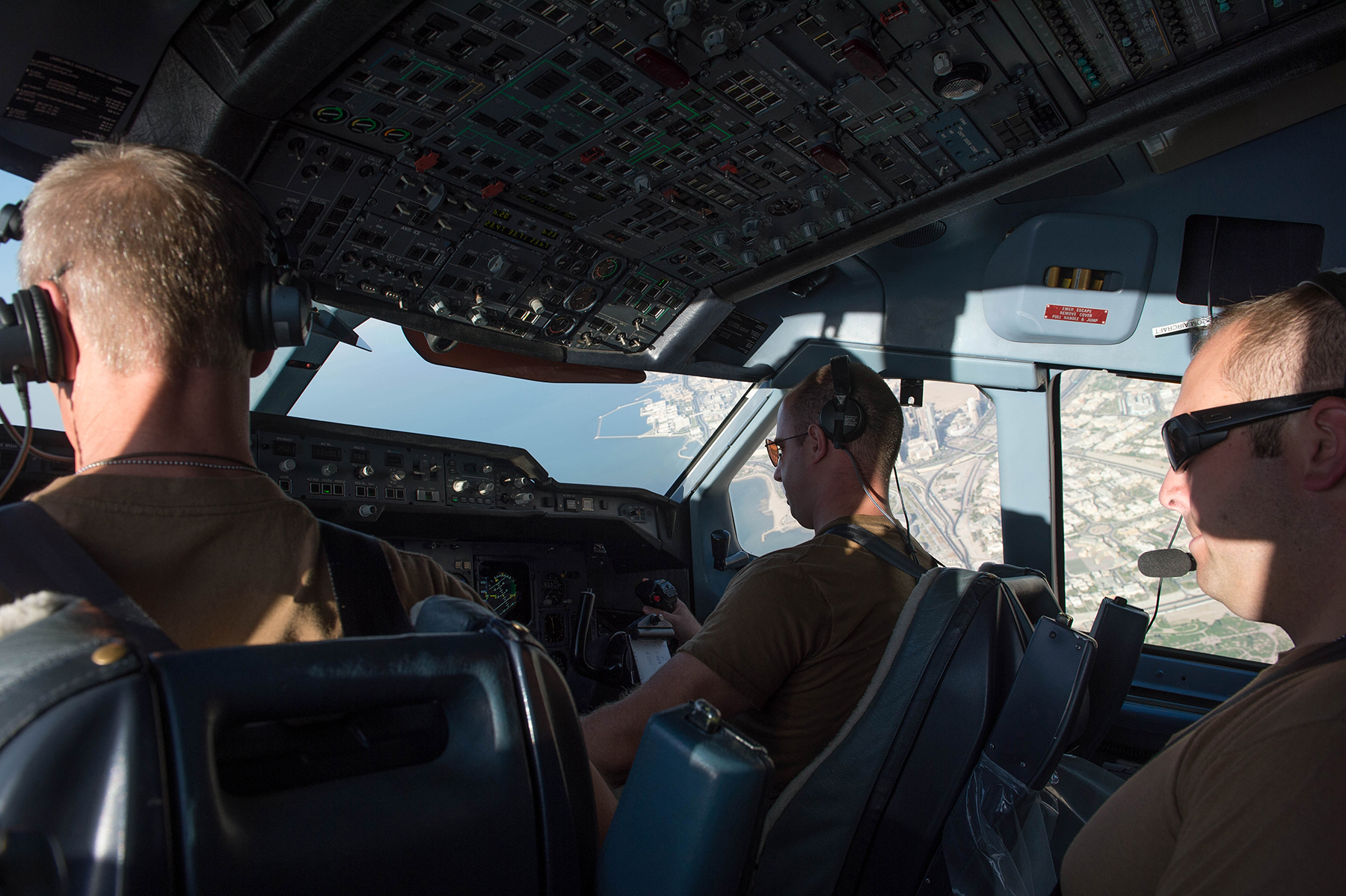 In a cockpit, three men in khaki t-shirts fly an aircraft over a sea port.