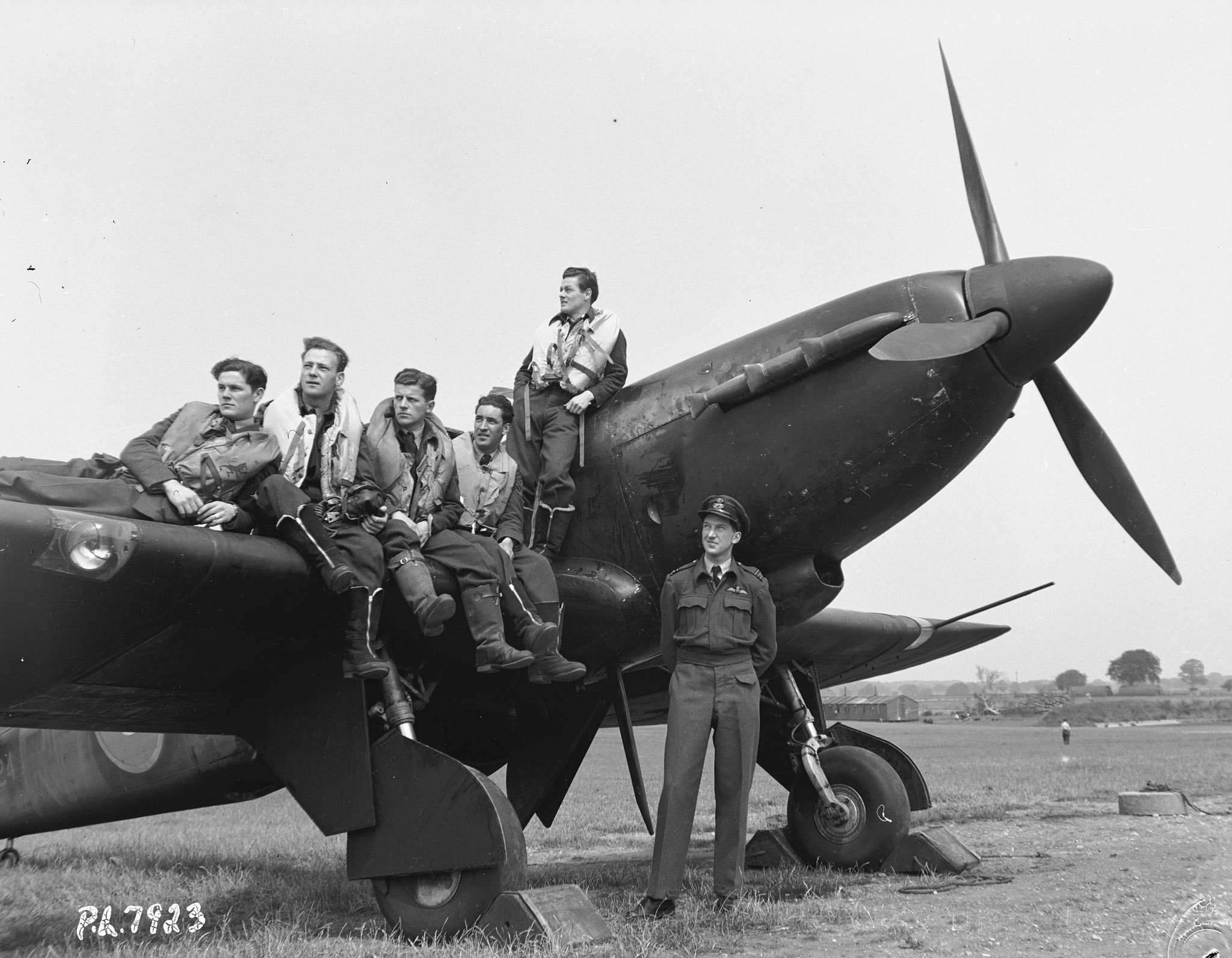 "The original caption of this June 25, 1942, photo reads: ""In many of the Royal Air Force squadrons overseas, groups of Canadians, graduates of the British Commonwealth Air Training Plan, will be found. Here is a typical group with an RAF fighter squadron. From left to right, they are: Pilot Officer R.A. Dunn of Lyons Brook and Pictou, Nova Scotia; Flight Sergeant F.S. Marsh of Montreal; Flight Sergeant Bill Sanders, of Headingley, Manitoba; Flight Sergeant Bill Hane, of Charlow [sic], Nova Scotia, Flight Sergeant E. Ingram of Saint John, New Brunswick; and Squadron Leader Thornton Brown, a member of the RAF."" PHOTO: DND Archives, PL-7923"