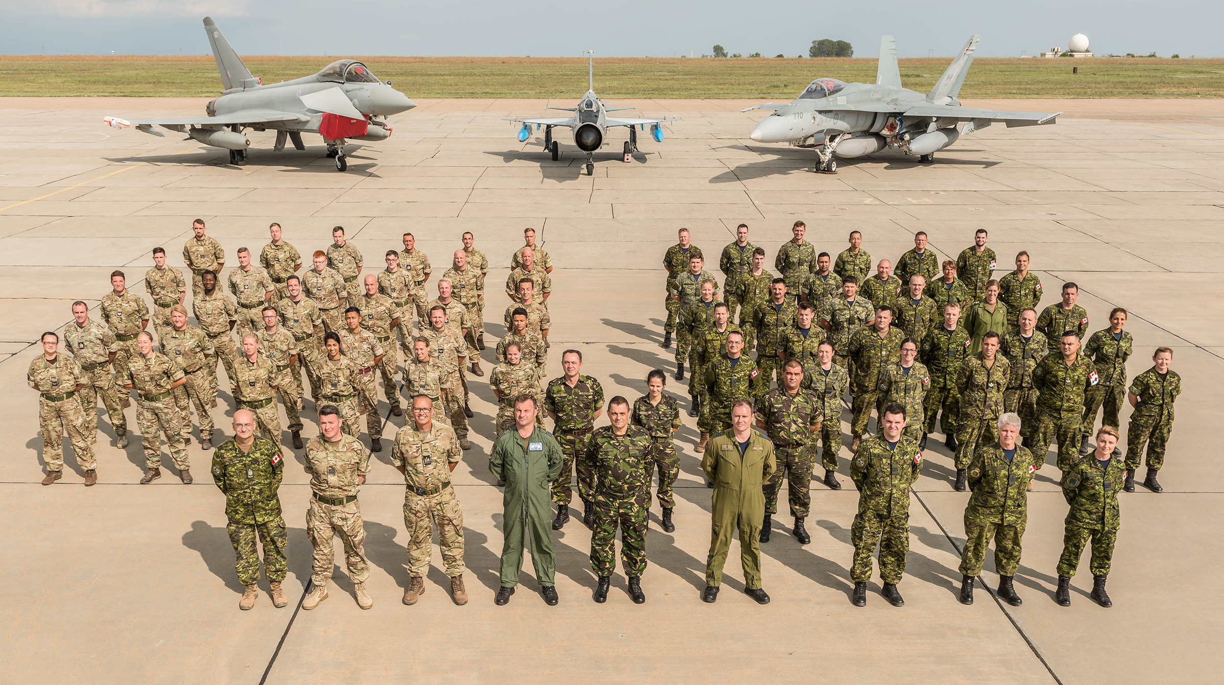 A group of people in military combat uniforms stand on a tarmac outdoors with aircraft behind them.