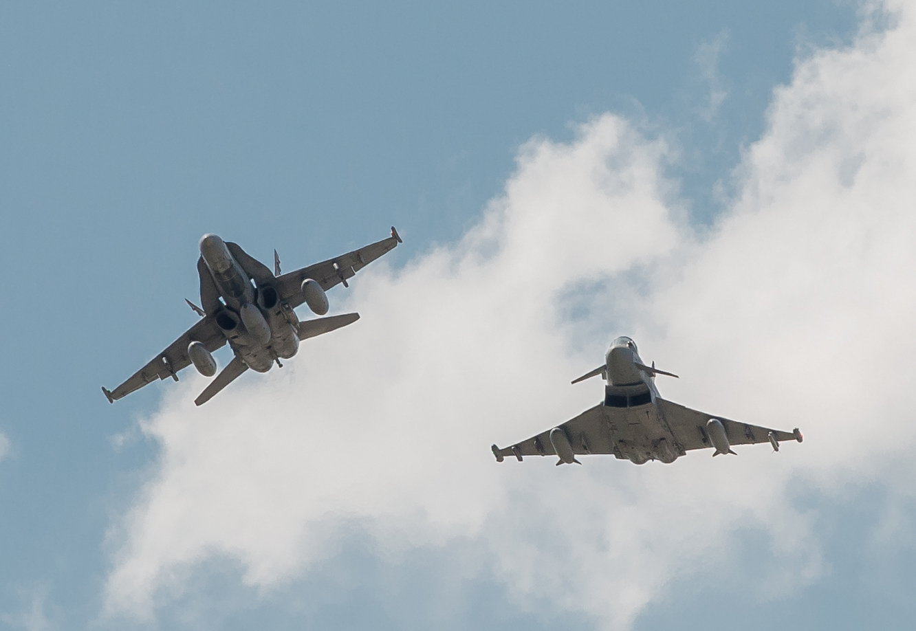 A Royal Canadian Air Force CF-188 Hornet and a Royal Air Force Typhoon FGR4 aircraft fly over Mihail Kogalniceanu Air Base, Constanta, Romania on August 23, 2017, during Operation Reassurance in support of NATO enhanced Air Policing. PHOTO: Sergeant Daren Kraus RP14-2017-0010-01