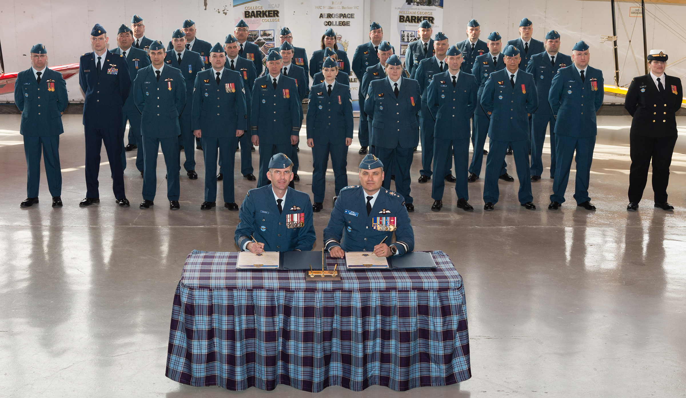 Two men in military uniforms sit at a table covered in tartan cloth and a group of military personnel stand behind them.