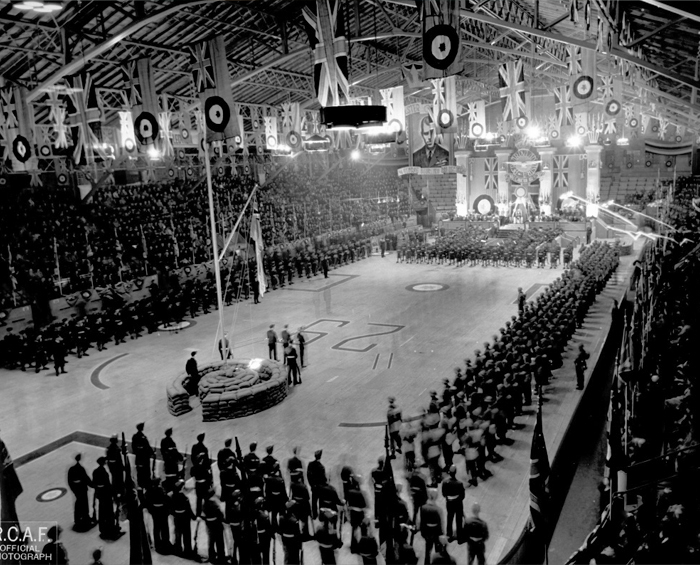 A massive turnout greeted Flight Sergeant George Beurling at his hometown arena in Verdun, Québec, now part of Montreal. After being wounded at Malta and returning to Great Britain, he was sent to Canada to join a Victory Loan Drive. He sold war bonds, was the guest of honour at a parade in Verdun, and met Prime Minister Mackenzie King. He did not enjoy the war bond campaign. Also, he often said things that embarrassed the RCAF, such as that he enjoyed killing people. The leg wound Beurling had received over Malta, combined with his poor general health, returned him to hospital for several weeks. He completed his promotional work in mid-1943, and met his future wife, Diana Whittall, in Vancouver, British Columbia. PHOTO: RCAF