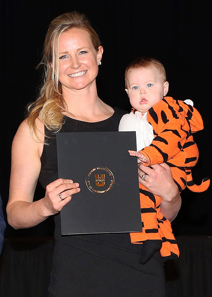RCAF Captain Stephanie Dennis holds her daughter and the Academic All Canadian award certificate she received from Dalhousie University. Her daughter is dressed as the Dalhousie mascot. PHOTO: Dalhousie Athletics