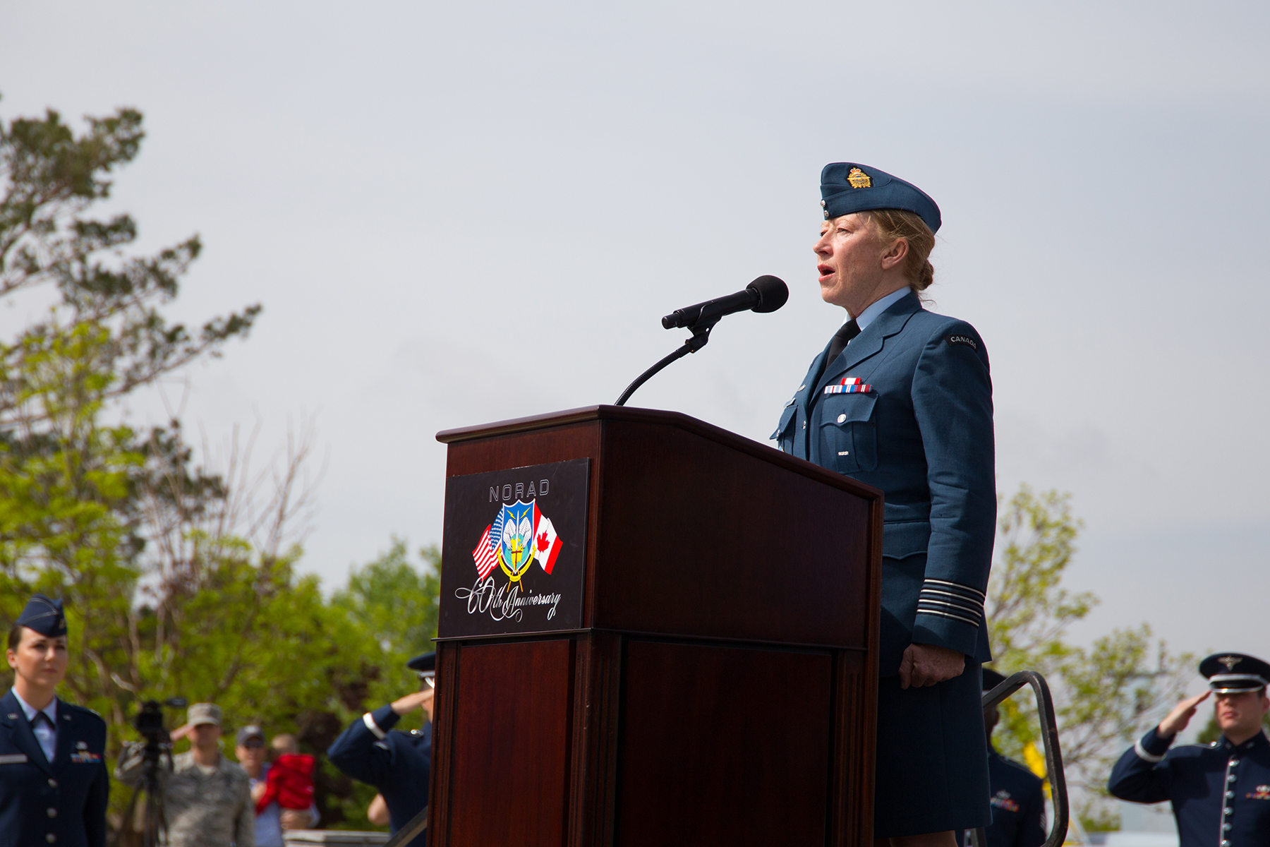 Royal Canadian Air Force Honorary Colonel Loreena McKennitt sings the Canada and U.S. National Anthems during the unveiling ceremony for a memorial cairn outside the NORAD and USNORTHCOM headquarters building at Peterson Air Force Base, Colorado, on May 11, 2018. The cairn honors the Canadian service men and women who died while serving at NORAD. PHOTO: U.S. DoD, N&NC Public Affairs
