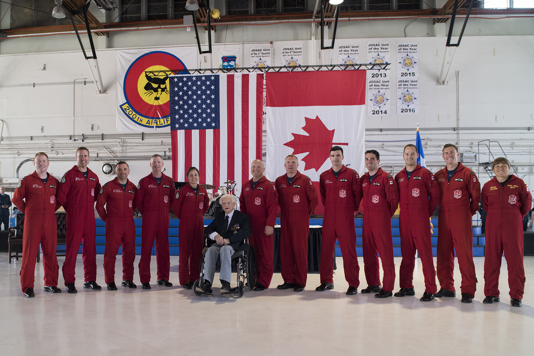 Members of the Canadian Forces aerial demonstration team The Snowbirds pause for a photograph with Second World War Squadron Leader George Sweanor (retired), 98, during the North American Aerospace Defense Command's (NORAD's) 60th anniversary ceremony at Peterson Air Force Base,  Colorado, on May 12, 2018. PHOTO: U.S. DoD, Staff Sergeant Emily Kenney