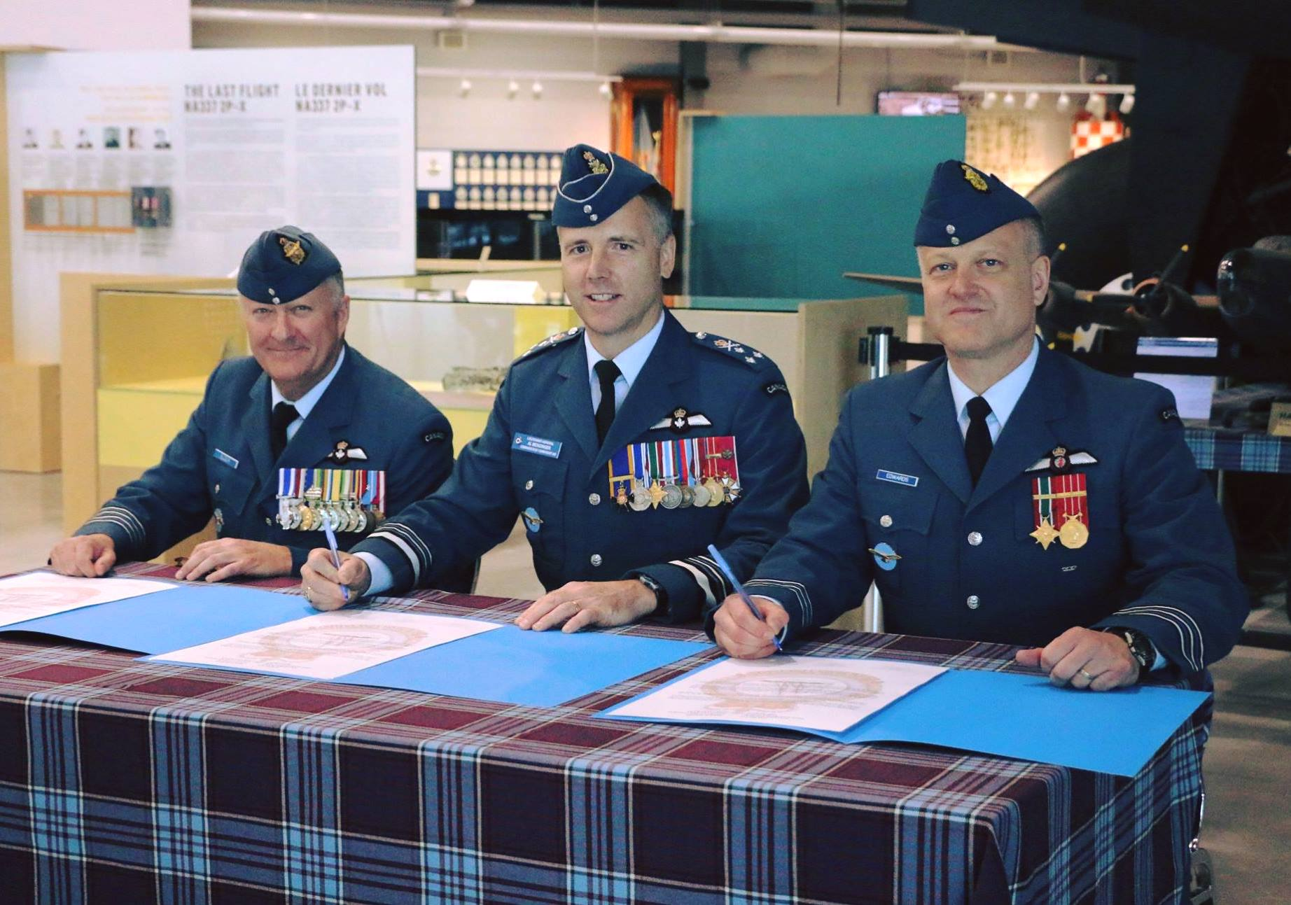 Three men in uniform sit at a tartan-covered table with documents in front of them.