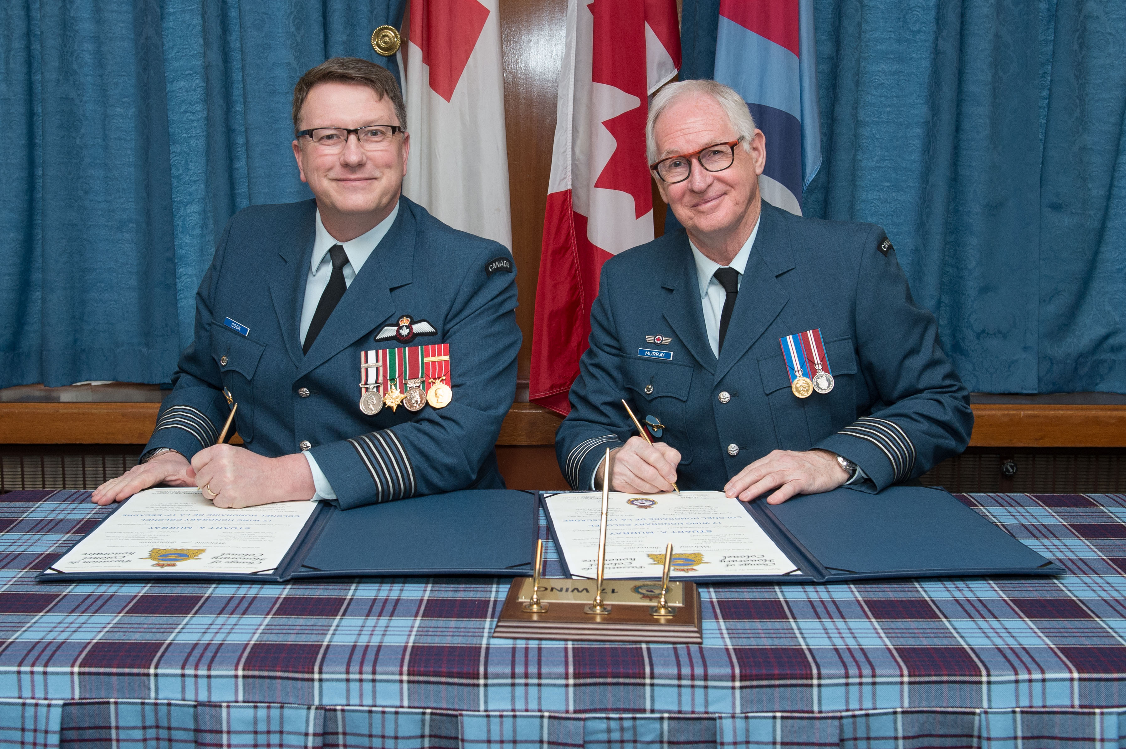 With flags in the background, two men wearing blue uniforms with medals sit at a tartan-covered table signing documents.