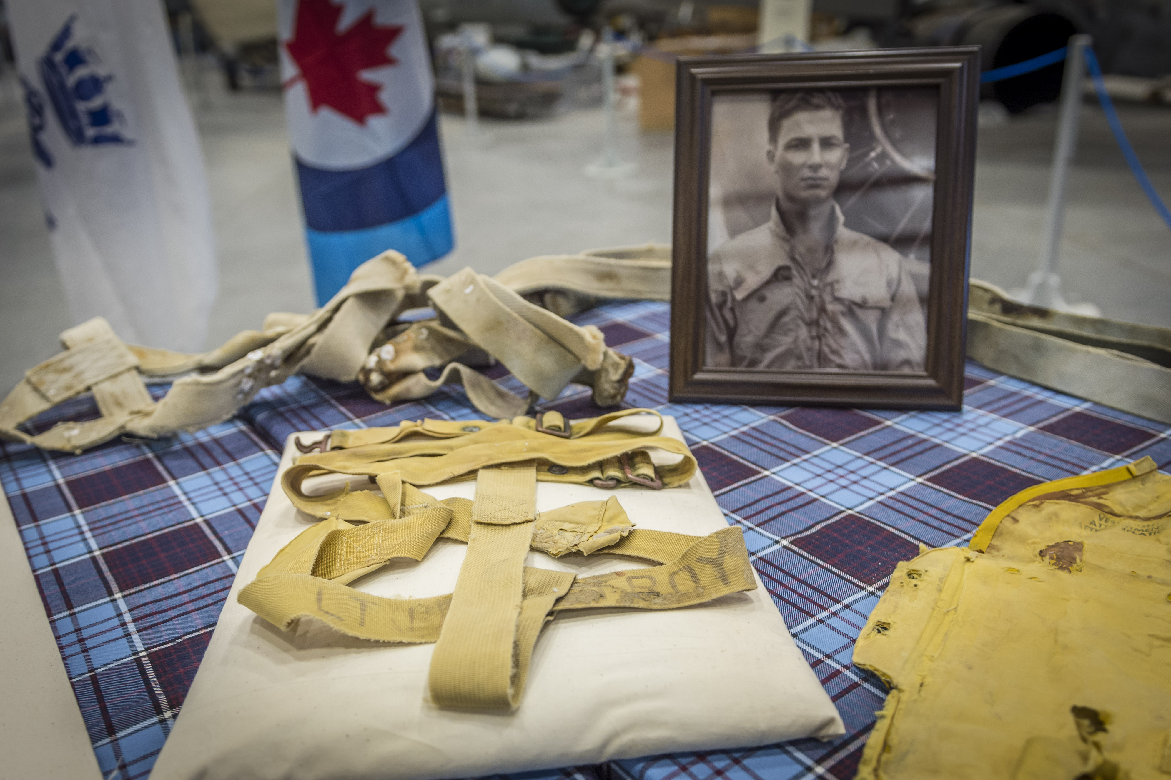 Items worn by Lieutenant Barry Troy when he crashed rest on a table beside his portrait at the Canada Aviation and Space Museum. PHOTO: Corporal Alana Morin, FA03-2018-0038-021