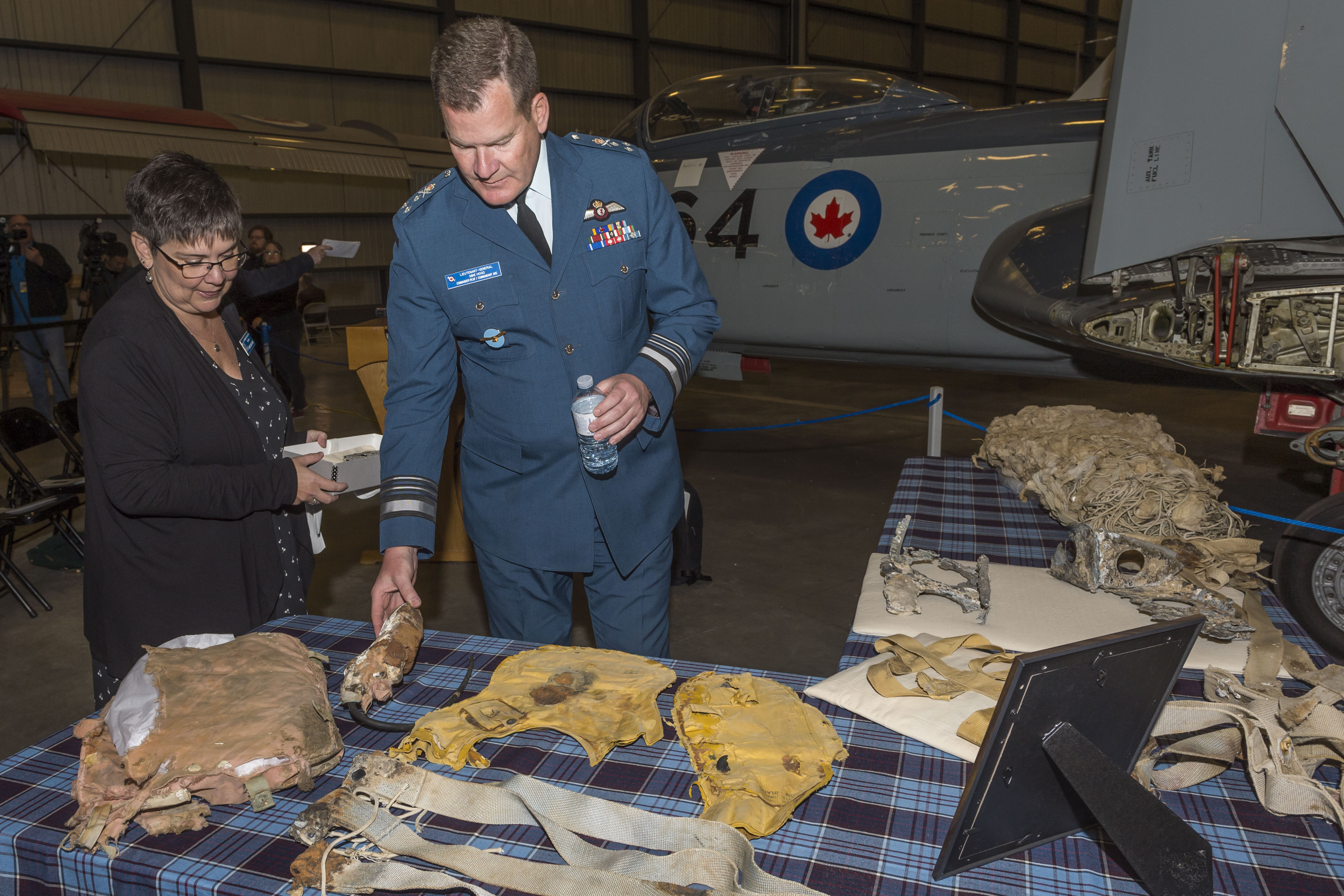 Ms. Christine Hines, curator of the Shearwater Aviation Museum, and Lieutenant-General Mike Hood, commander of the RCAF, examine artifacts relating to Lieutenant Barry Troy in the Annex of the Canada Aviation and Space Museum. In the background is a Banshee fighter, similar to the one Lieutenant Troy was flying when he crashed in 1958. PHOTO: Corporal Alana Morin, FA03-2018-0038-029