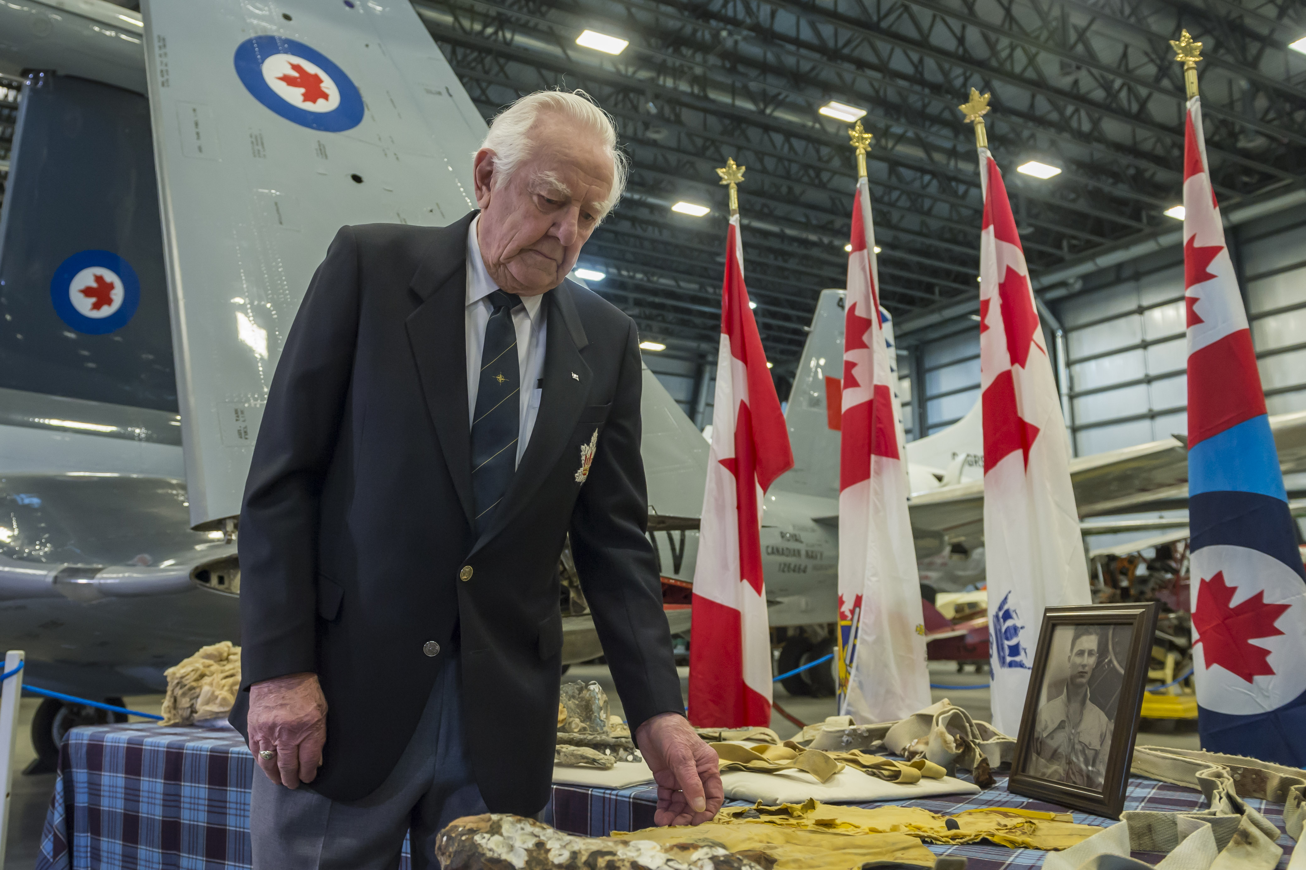 Mr. Bruce Baker, examining the artifacts at the invitation of Padre Askew, was a Royal Canadian Navy Tracker pilot and friend of Lieutenant Troy's. PHOTO: Corporal Alana Morin, FA03-2018-0038-042