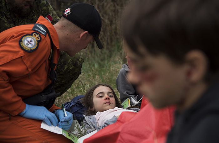 slide - A person wearing orange clothing tends to a girl with simulated injuries.