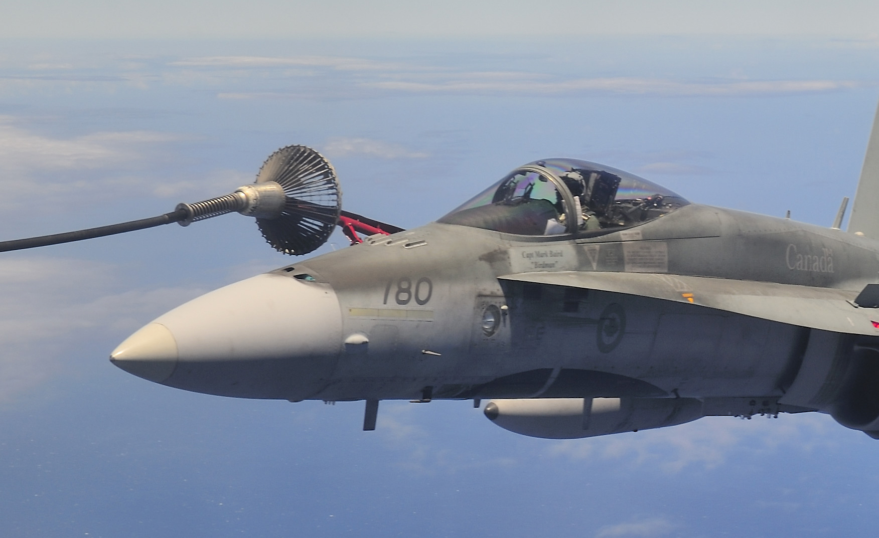 "On July 25, 2012, an RCAF CC-130HT Hercules air-to-air refueller from 435 Transport and Rescue Squadron, tops up a CF-188 Hornet from 409 Tactical Fighter Squadron in Cold Lake, Alberta, over the Pacific Ocean near Joint Base Pearl Harbor-Hickam, in Honolulu, Hawaii, on July 25, 2012. Both were participating in Exercise Rim of the Pacific (RIMPAC). This photo illustrates the ""probe and drogue"" method that the RCAF uses for refuelling. The probe is the mechanism on the fighter and the drogue is the basket attached to the hose through which the fuel is pumped. PHOTO: Master Marc-André Gaudreault, IS2012-2003-154"