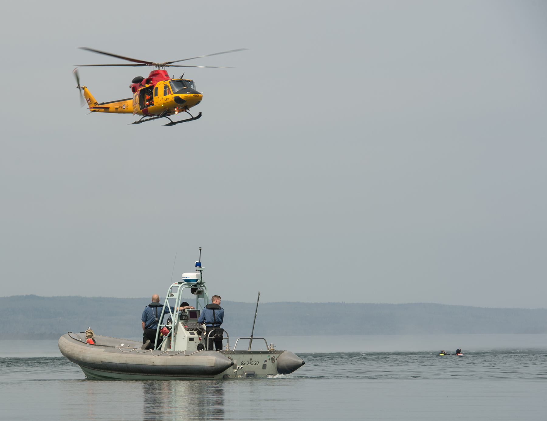 During Chinthex 18, a CH-146 Griffon helicopter from 439 Combat Support Squadron approaches people in the water near a rigid-hulled inflatable boat and crew from Naval Reserve unit HMCS Griffon. PHOTO: Corporal Bryce Cooper, WG2018-0229-004
