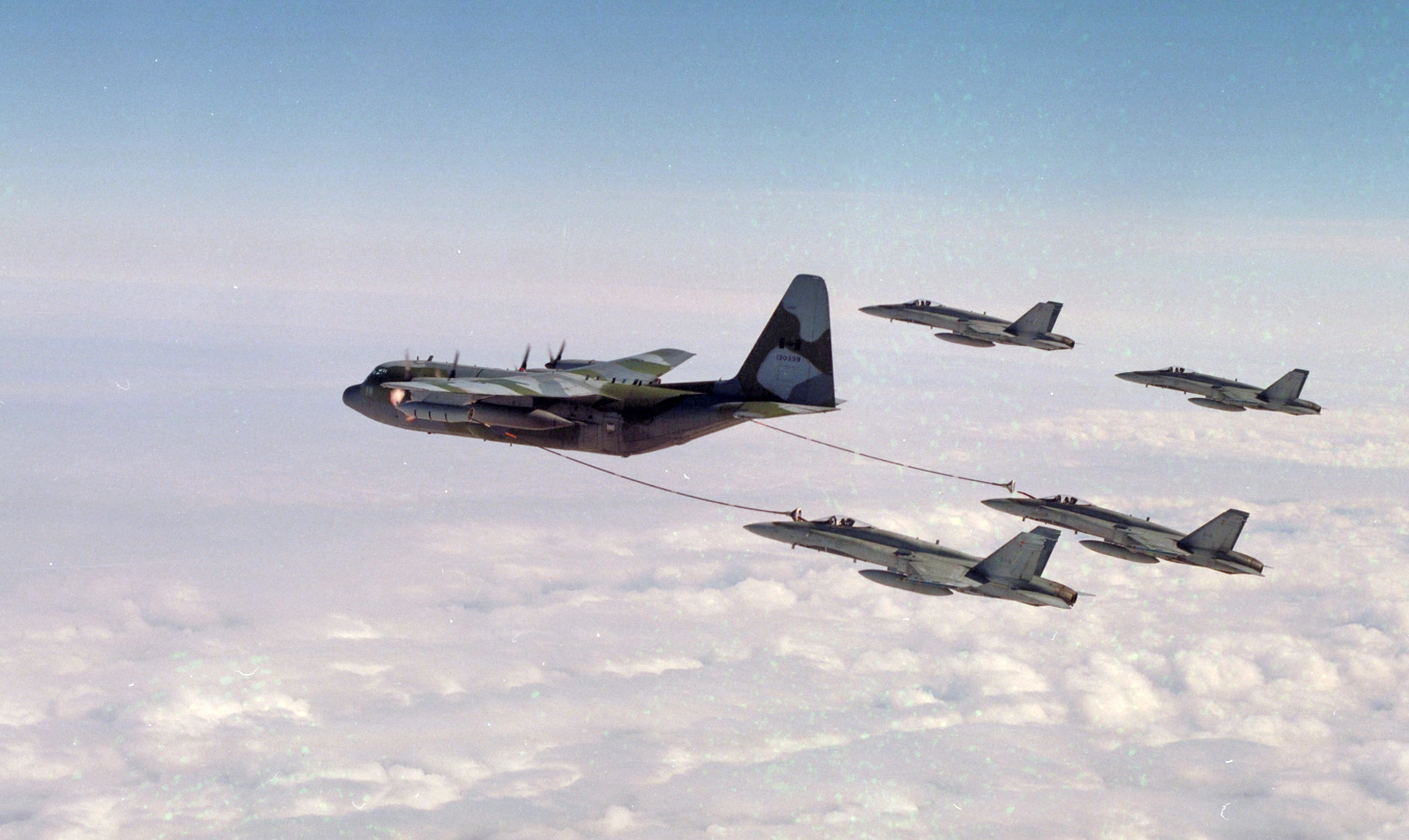 A CC-130HT Hercules air-to-air refuelling from 435 Squadron refuels four CF-188 Hornets from 416 Squadron, circa 1995. PHOTO: DND, WGC95-288-44A