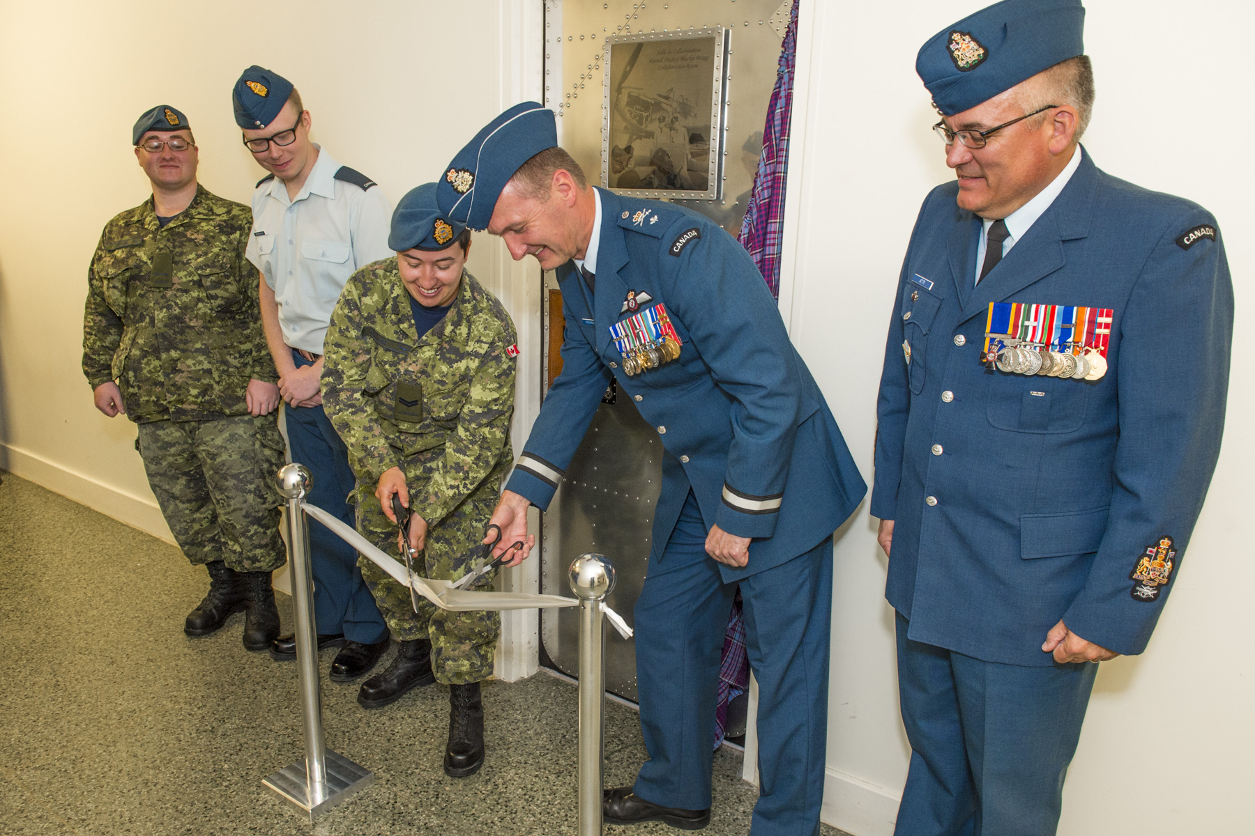 Five people, in various military uniforms stand with a door behind them. Two of them use scissors to cut a ribbon strung between two metal posts in front of them.