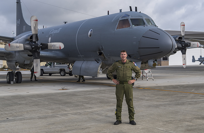 A man wearing a military uniform stands in front of a large military aircraft.