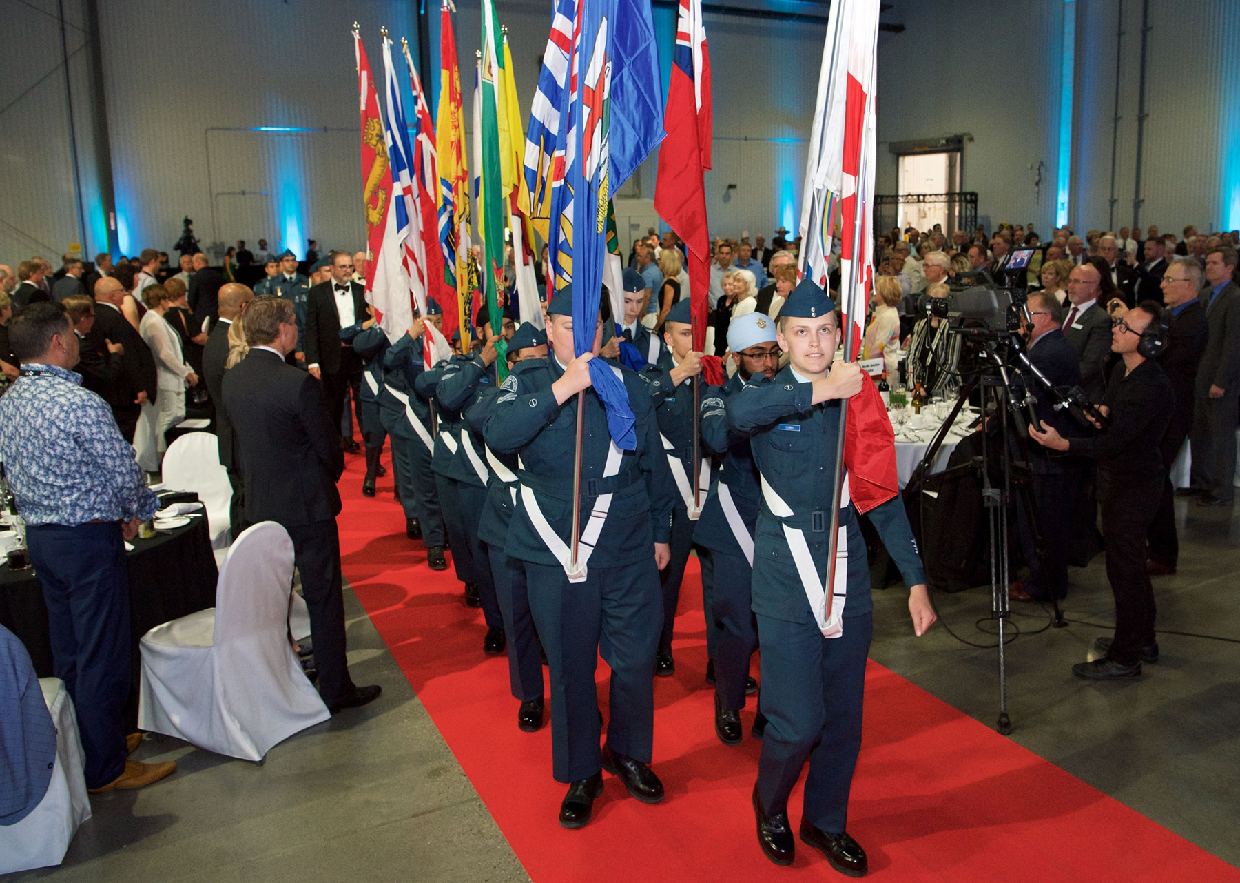 "As per tradition, a Colour Party of air cadets leads 2018 Aviation Hall of Fame inductees into the 2018 Induction Ceremony dinner. In 2018, members of 538 ""Buffalo"" Squadron carried the Canadian flags in the procession, led by the Calgary Police Serve Pipe Band. PHOTO: Rick Radell"