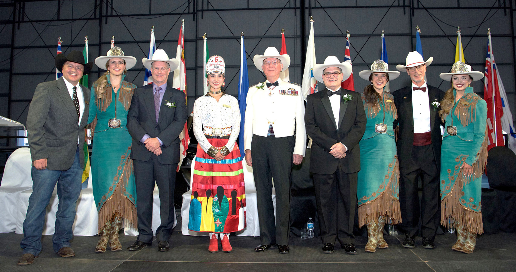Wearing their newly received white Smithbilt cowboy hats, from left, Iain Bogie, representing his late father, John Bogie; Paul Manson; John Maris; and Greg Powell stand with the Calgary Stampede Queen and Princesses, and the Stampede vice-president Steve McDonough (far left). During the White Hat Ceremony, the CAHF inductees pledged to spread the Calgary brand of friendship and hospitality. PHOTO: Rick Radell
