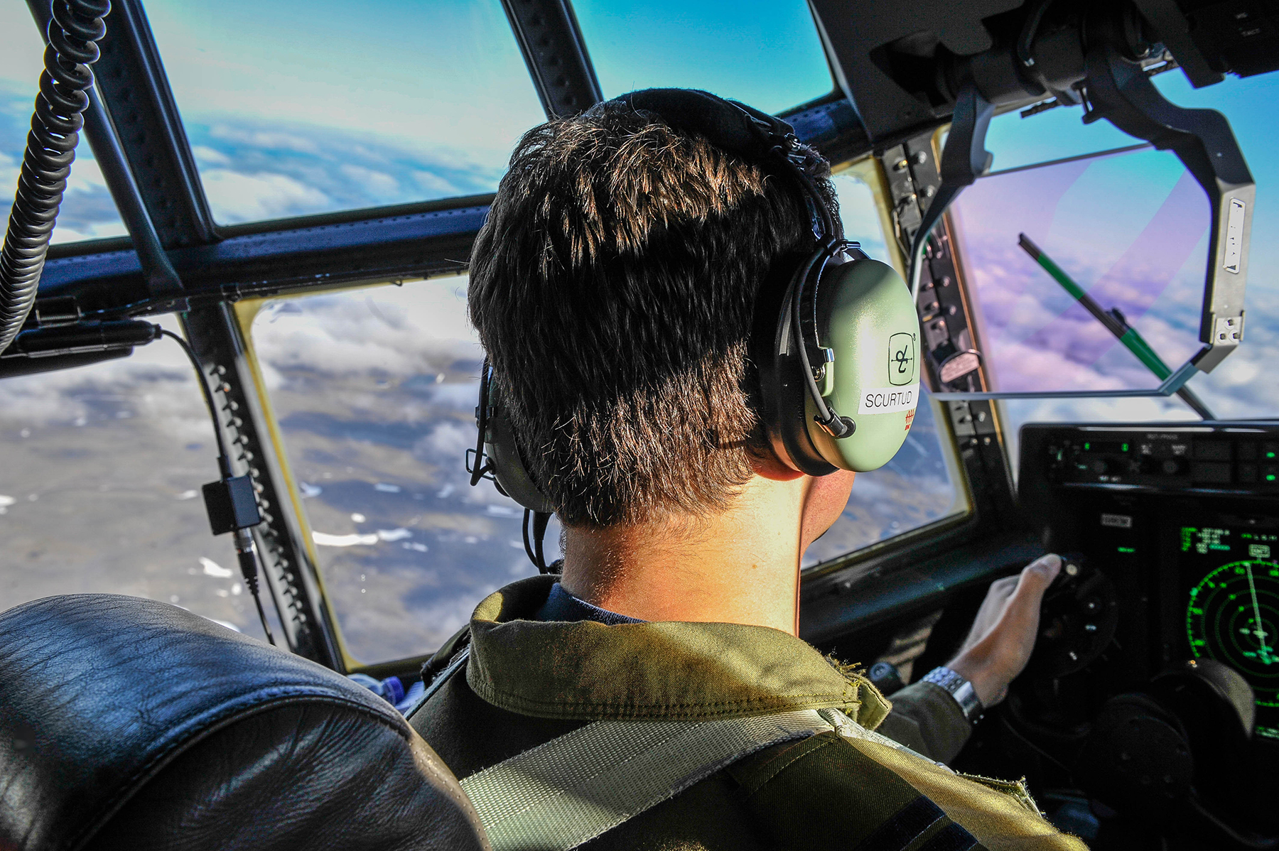 A man pilots an aircraft above rough terrain and clouds.