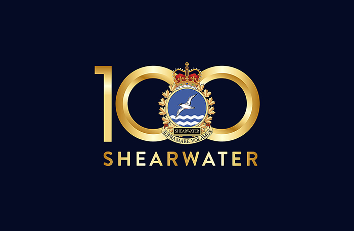"slide - A very dark blue logo with a gold and blue military crest over the number ""100"" written in gold characters. Under the crest is the word ""SHEARWATER"", also printed in gold characters."