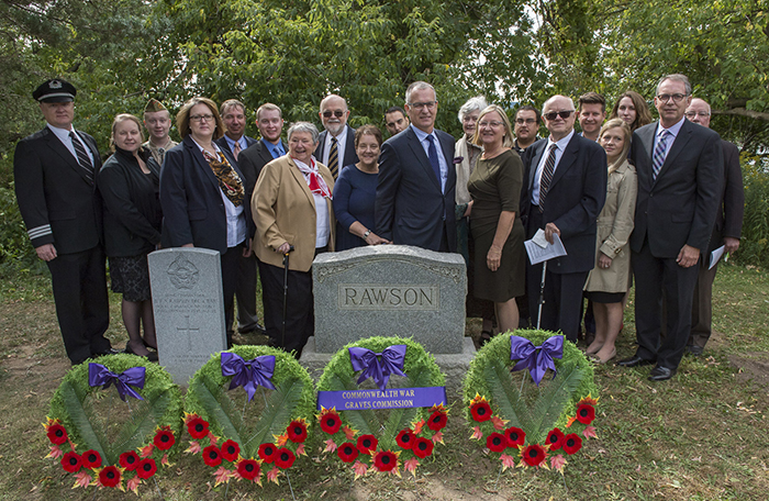 A group of 20 men and women wearing civilian clothes stand behinds behind two grave stones, in front of which are four remembrance wreaths decorated with poppies.