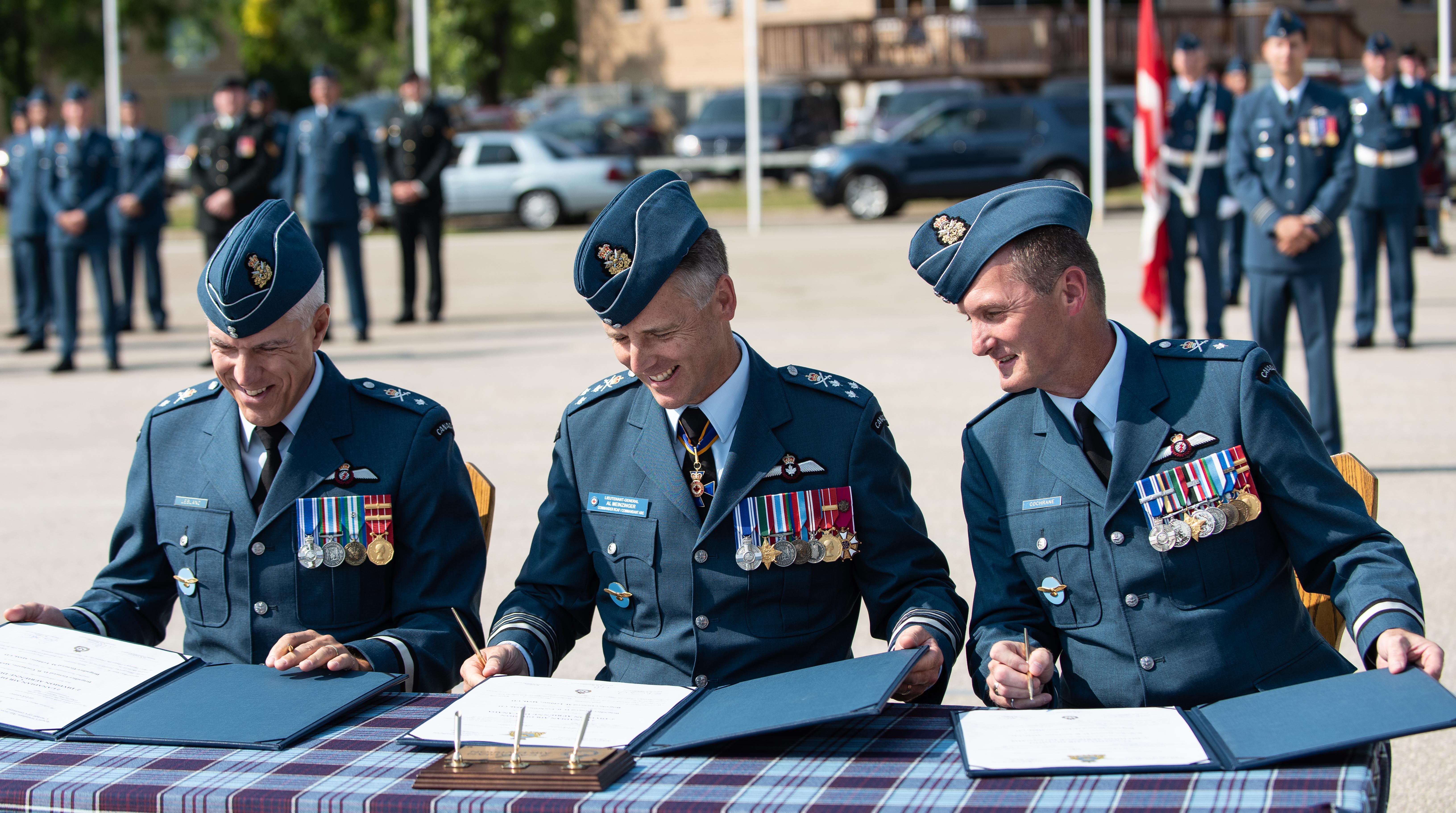 Three men in military uniforms, with medals on their tunics, sit behind a table outdoors with documents in folders in front of them.