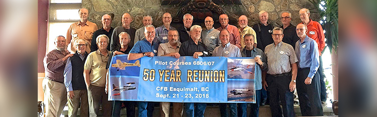 "slide - A group of men stand in two rows in front of a stone fireplace. Several hold a large banner reading ""50 Year Reunion""."