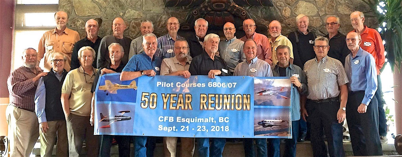 "A group of men stand in two rows in front of a stone fireplace. Several hold a large banner reading ""50 Year Reunion""."