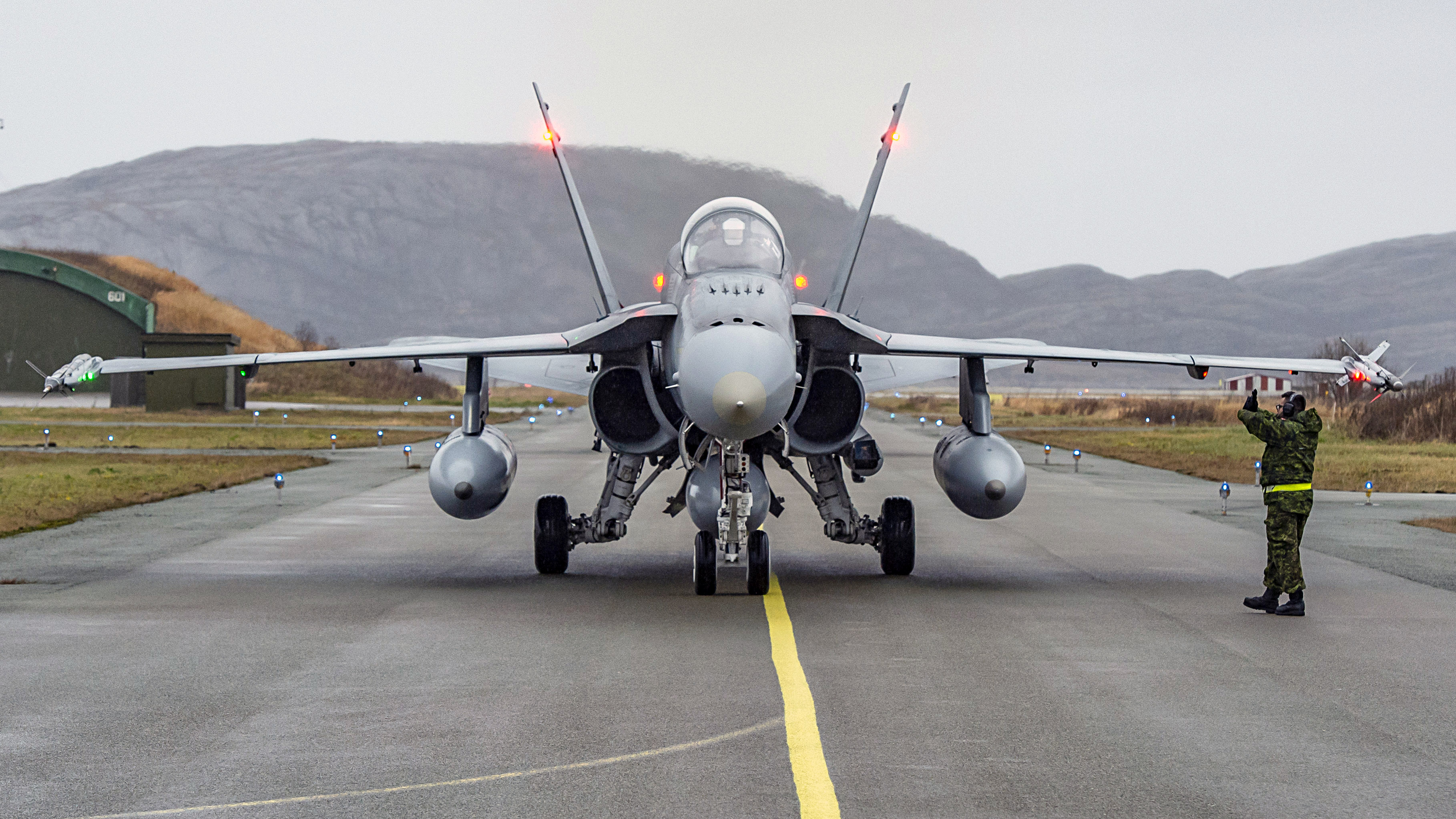 An aviation technician from 401 Tactical Fighter Squadron marshals a Royal Canadian Air Force CF-188 Hornet as it arrives to Bodo, Norway on October 19, 2018, in preparation for Exercise Trident Juncture 2018. PHOTO: Corporal Bryan Carter, CK04-2018-0922-004