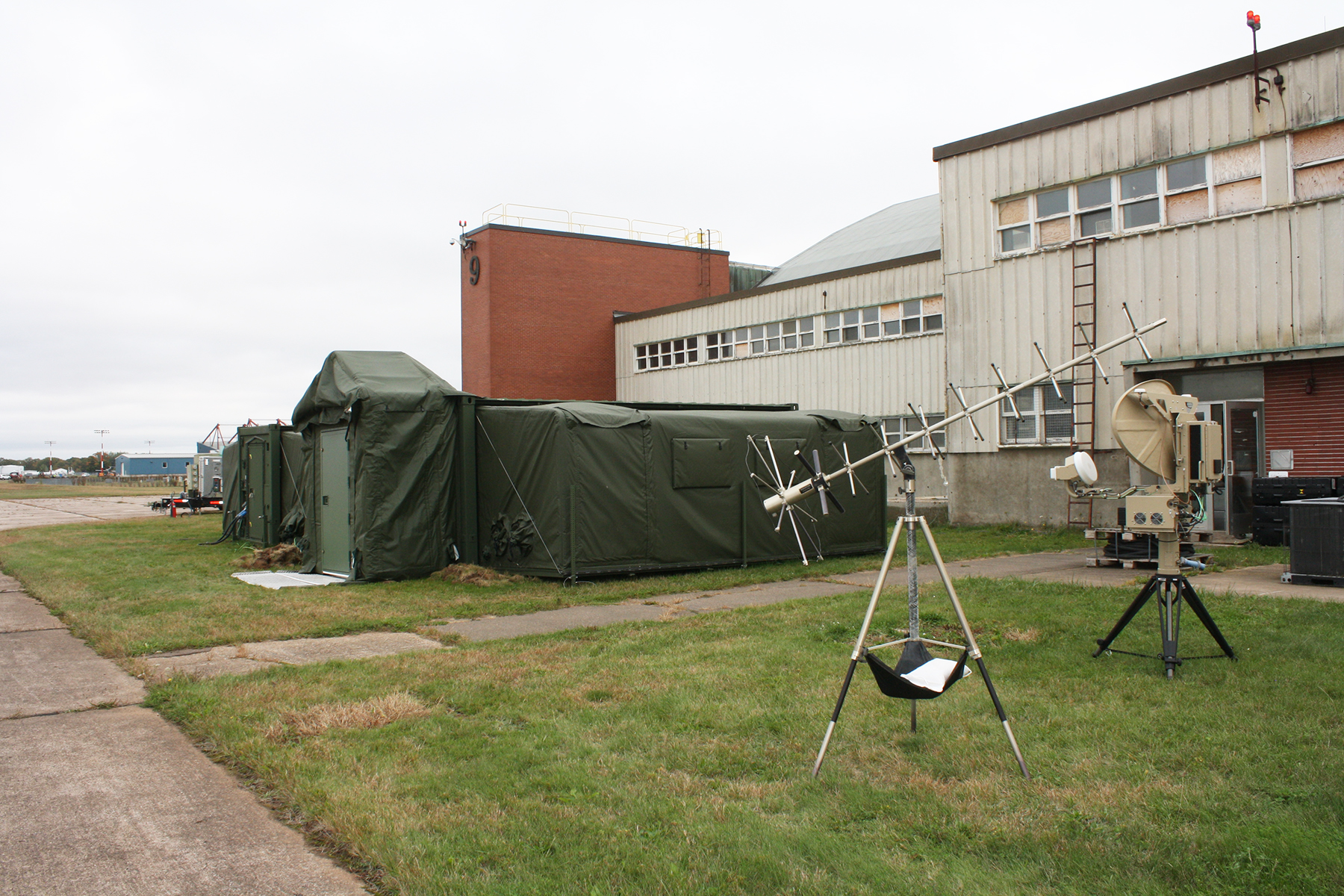 A large olive-green tent sits on the grass alongside a building.