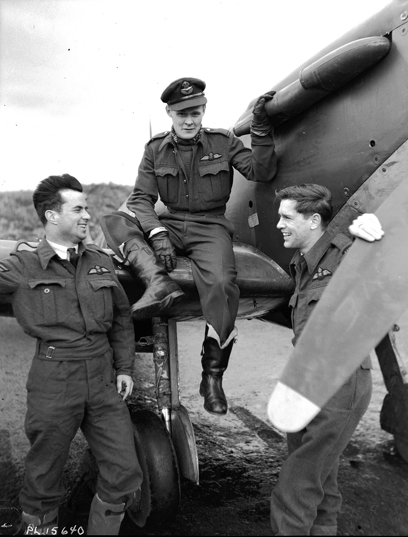 In a black and white photograph, a man in uniform sits on the wing of a vintage aircraft; two more stand beside the aircraft.