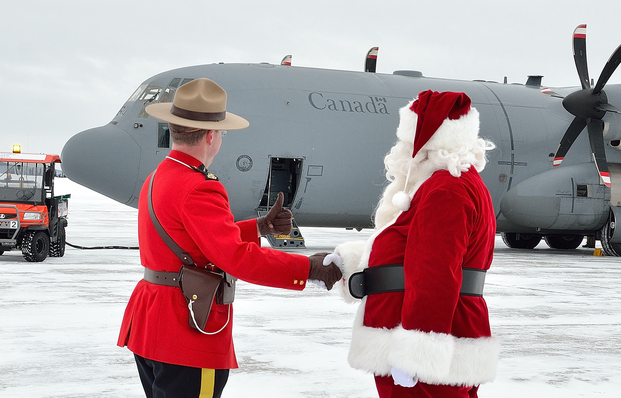 A member of the RCMP and Santa Claus shake hands in front of a large military cargo aircraft. The RCMP member gives a thumbs up signal.
