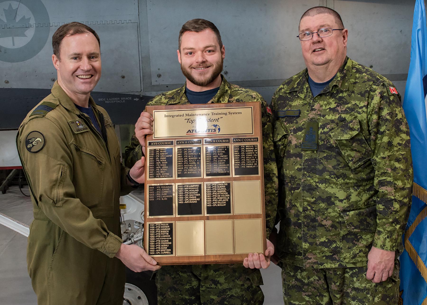 Three men wearing olive green or disruptive pattern uniforms stand in a row; with help from the man on the left, the man in the middle holds a large plaque.