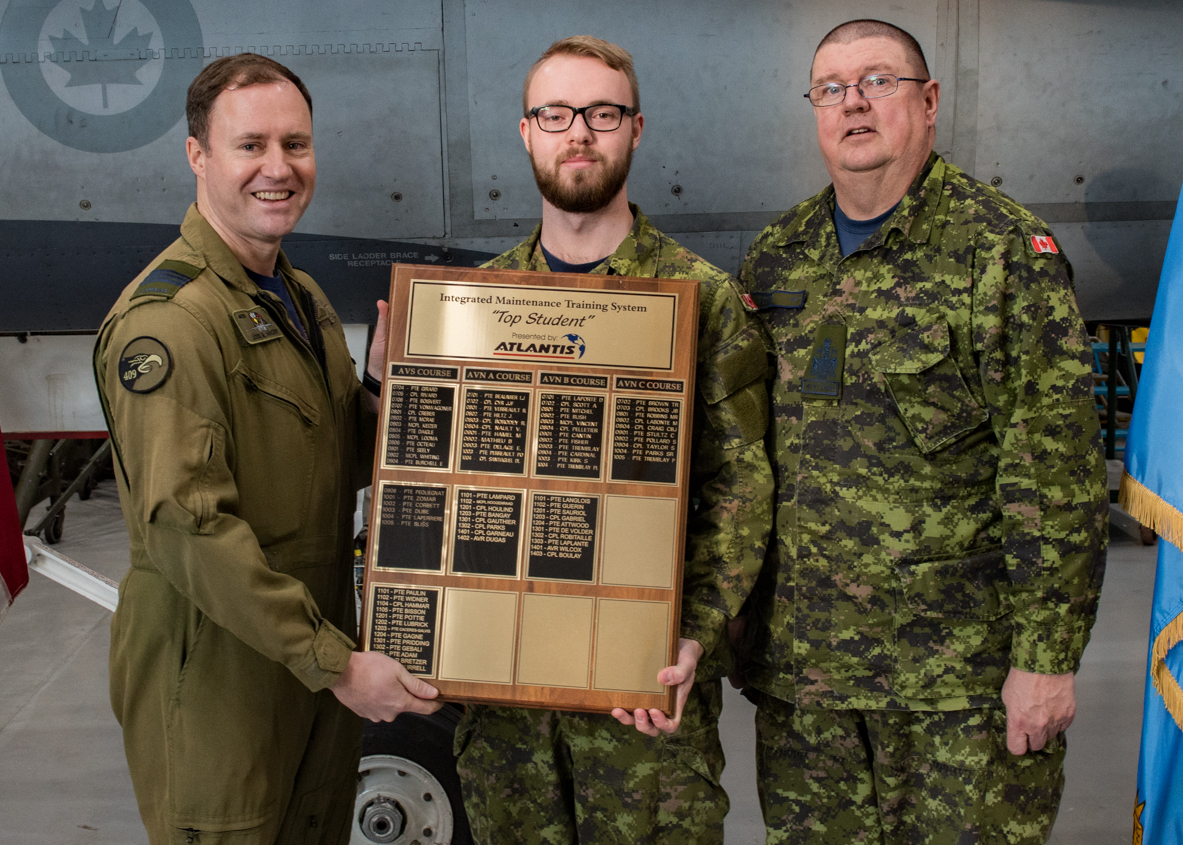 "Aviator Michael Richards, from 410 Tactical Fighter (Operational Training) Squadron, receives the top student award for his performance while on the air weapons systems ""on-type"" CF-188 course from Lieutenant-Colonel Mark Hickey, acting 4 Wing commander (left), and Chief Warrant Officer Terrance George. PHOTO: Corporal Maxime St-Cyr, FT2018-0051-026"