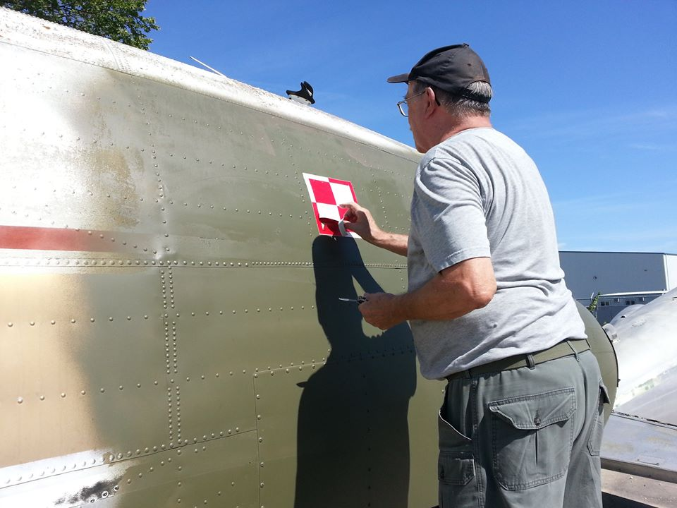 "A volunteer places the red and white insignia of the Polish air force on the fuselage of the ""Spirit of Ostra Brama"", a C-47 (DC-3) Dakota flown by Polish airmen serving with the Royal Air Force during the Second World War. The aircraft is being repatriated to Poland from 17 Wing Winnipeg, Manitoba. PHOTO: Submitted"