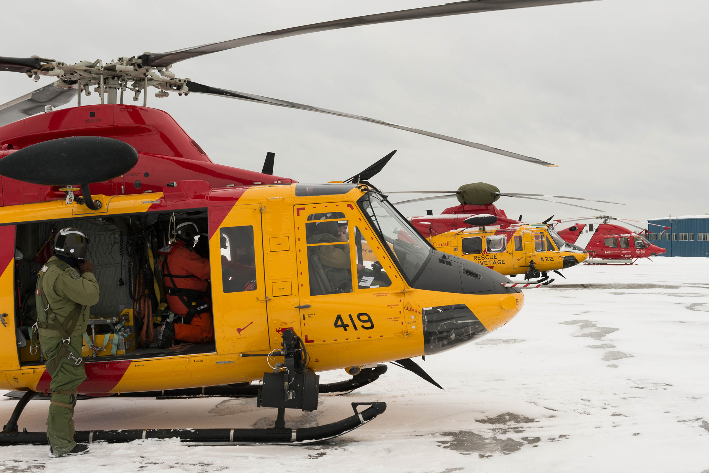 RCAF CH-146 Griffon helicopters and a Canadian Coast Guard helicopter rest on the tarmac as their crews prepare to resume the search for a missing civilian helicopter in the Timmins, Ontario, region on March 10, 2019. PHOTO: Corporal Zebulon Salmaniw, TN07-2019-0090-014