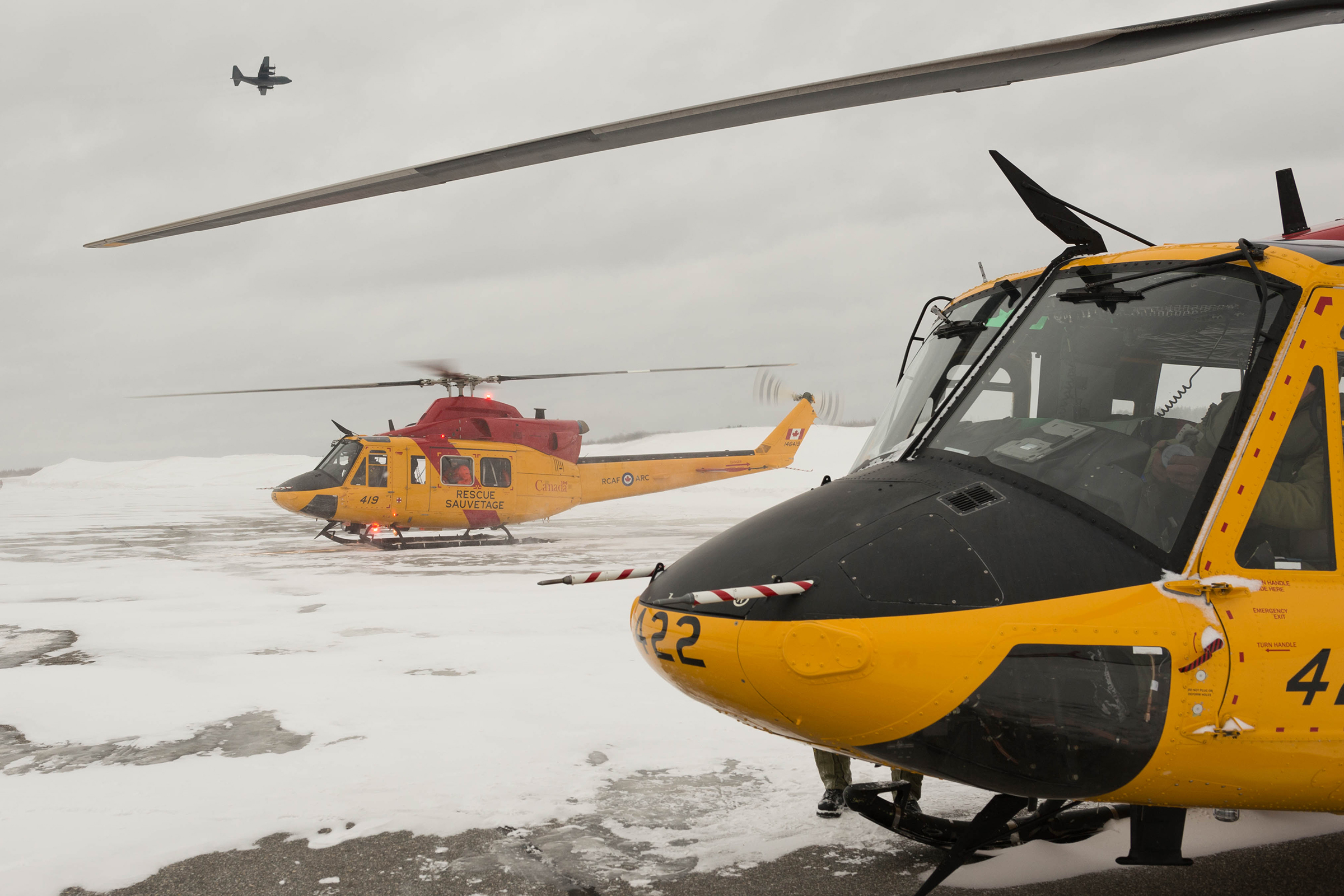 As an RCAF CC-130 Hercules flies overhead, two RCAF CH-146 Griffon search and rescue helicopters and their crews prepare to lift off from the snow-covered tarmac in Timmins, Ontario, on March 10, 2019, to resume the search for a missing civilian helicopter. PHOTO: Corporal Zebulon Salmaniw, TN07-2019-0090-019
