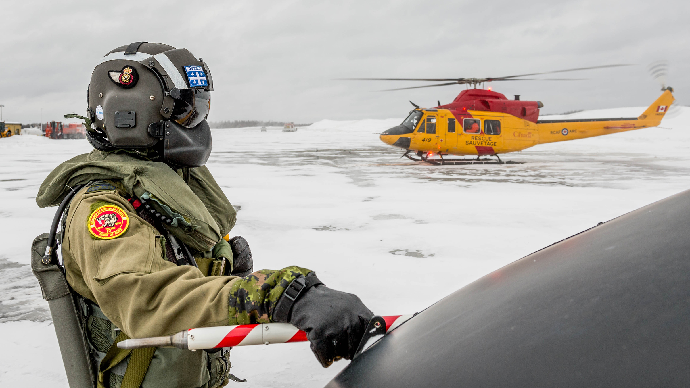 A person wearing a military flight suit and a full-visor flying helmet stands beside the nose of a helicopter with another helicopter in the background. The terrain is covered in snow.