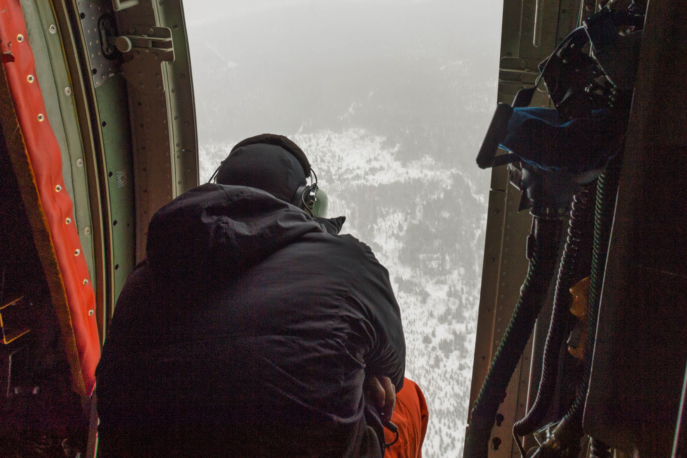 A search and rescue technician, onboard an RCAF CC-130 Hercules aircraft from 435 Transport and Rescue Squadron, based in Winnipeg Manitoba, watches the inhospitable terrain below during a search and rescue mission in the Timmins, Ontario, area on March 10, 2019. PHOTO: Corporal Zebulon Salmaniw, TN07-2019-0090-024