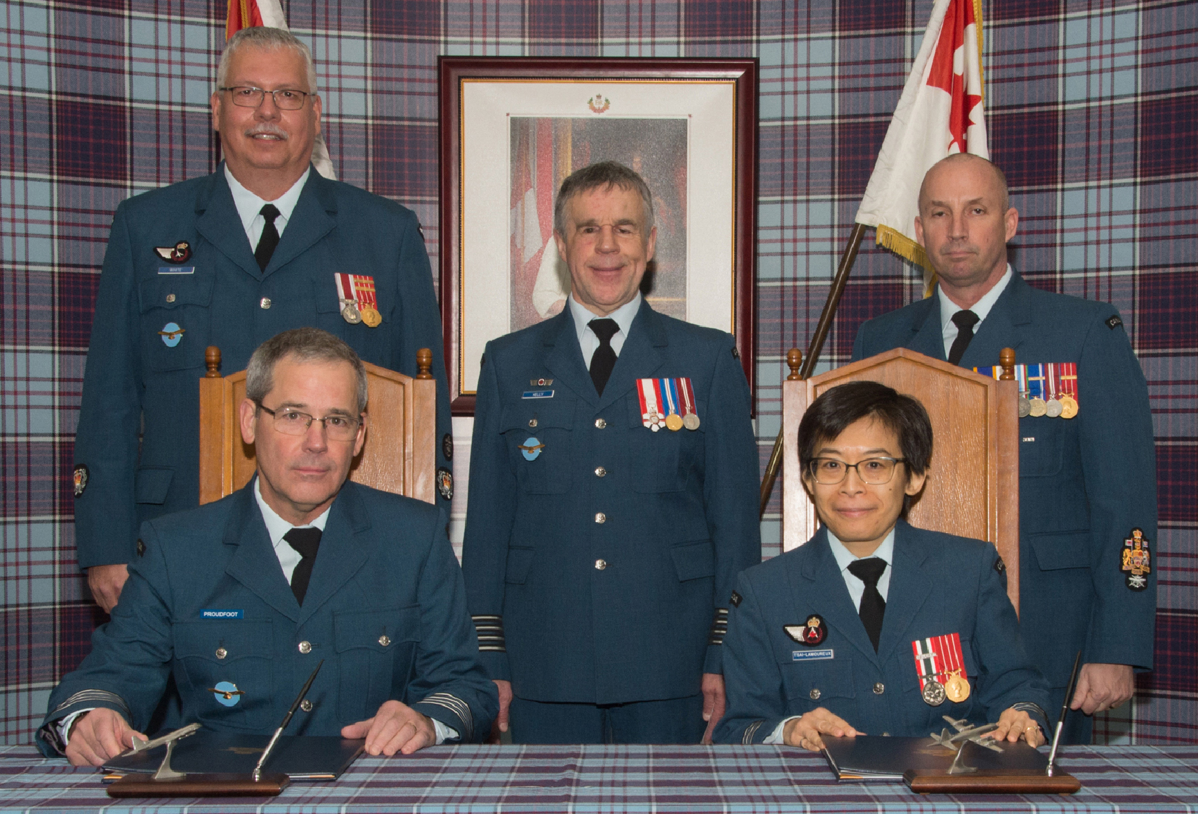 Four men and one woman, all wearing similar blue military uniforms, sit at or stand behind a table in front of a tartan backdrop displaying a framed photo; a flag stands on each side of the photo.